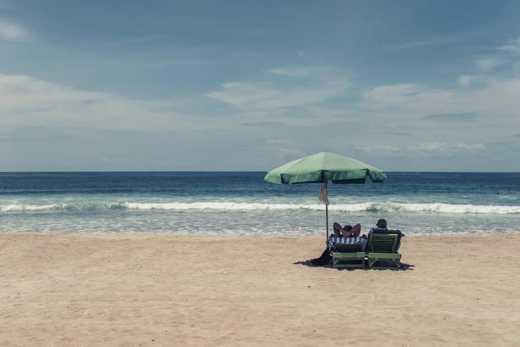 Foto de um casal ocupando espreguiçadeiras dobráveis em uma praia.