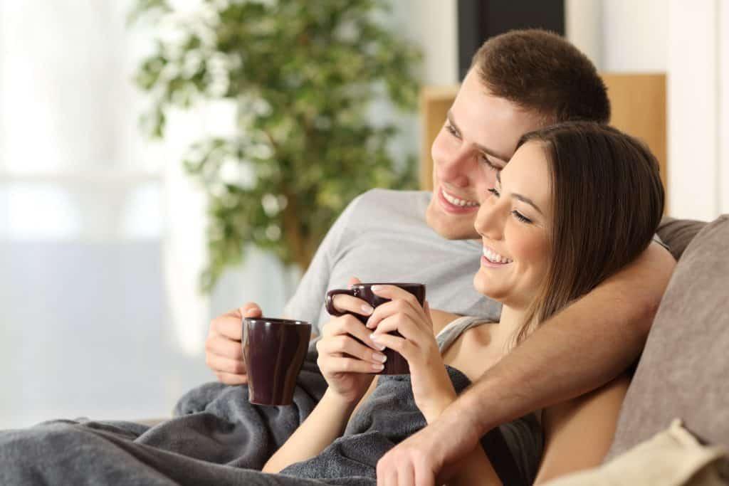 Imagem de um casal no sofá com canecas na mão e um cobertor de microfibra