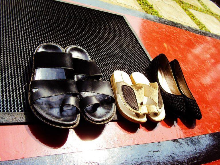Imagem de capacho de plástico sobre piso vermelho com um par de sapato feminino e dois pares de chinelos.