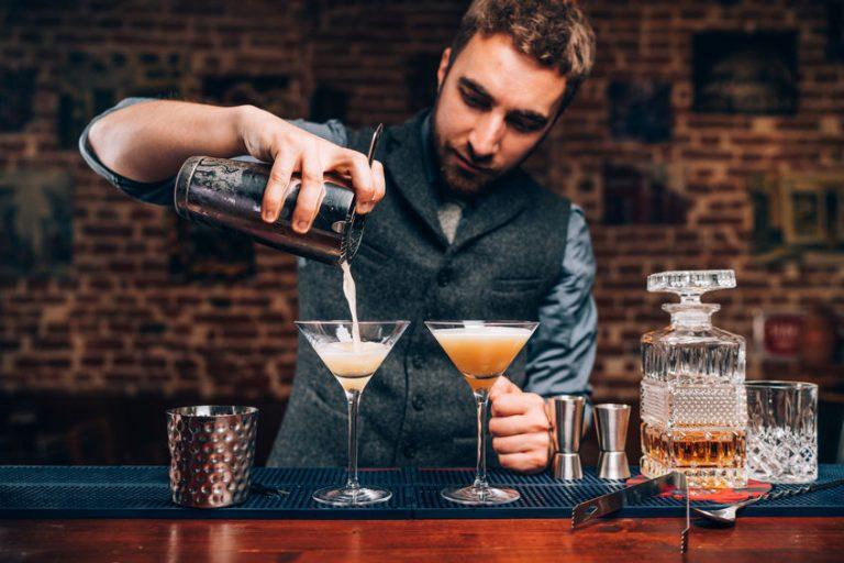 Bartender finaliza drink polvilhando ingredientes com auxílio de peneira