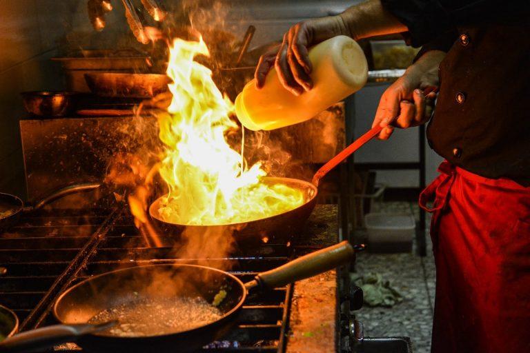 Imagem de chefe de cozinha preparando os alimentos em um fogão a gás industrial