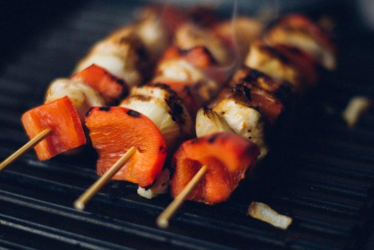 Imagem de kebabs de carne e legumes em chapa de ferro fundido