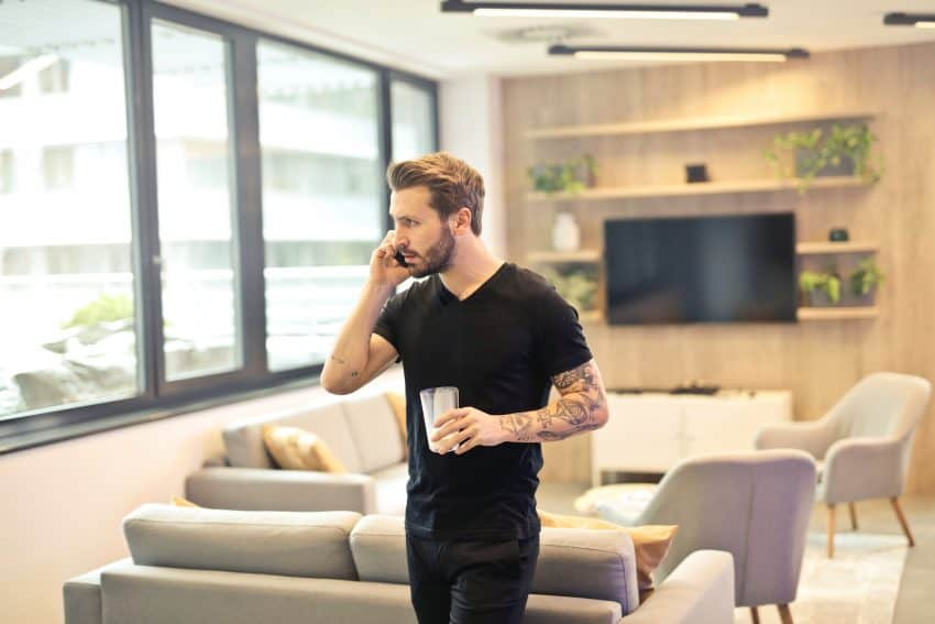 Na imagem encontra-se um homem vestido de preto falando ao celular segurando um copo com gelo. Ao fundo está uma sala de estar com sofás e poltronas na cor cinza claro, uma televisão, um armário pequeno branco e uma decoração com plantas.
