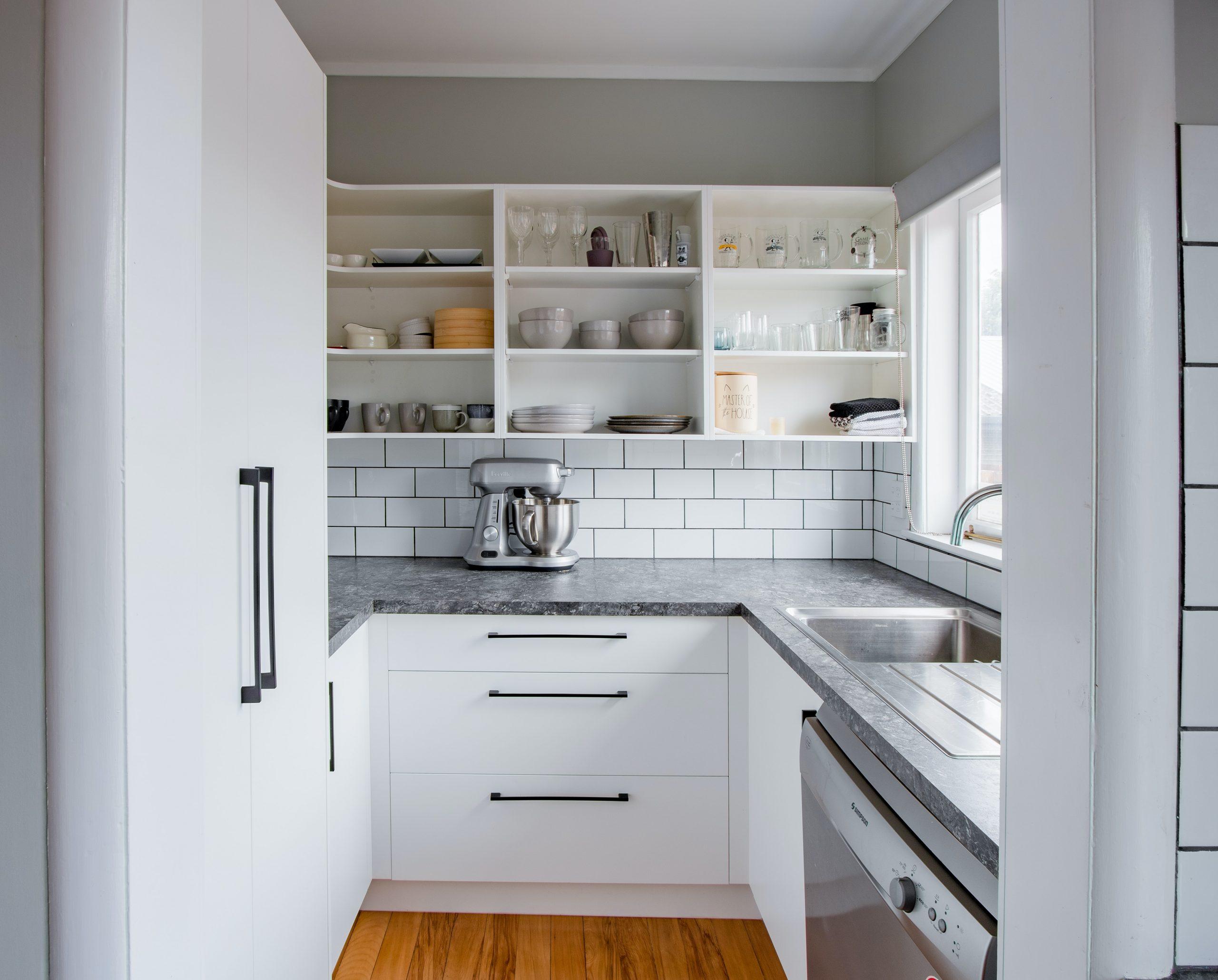 Na foto uma cozinha pequena com uma bancada cinza, revestimento quadriculado e prateleiras.