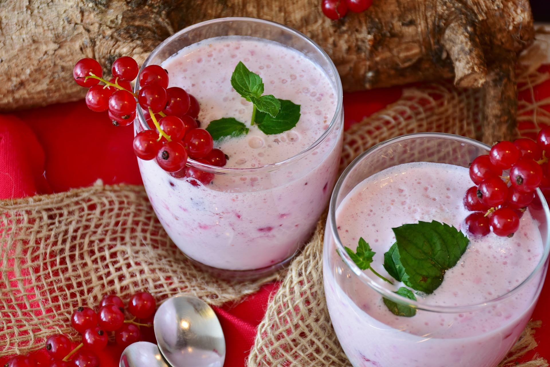 Dois copos de vidro com vitamina de frutas vermelhas.