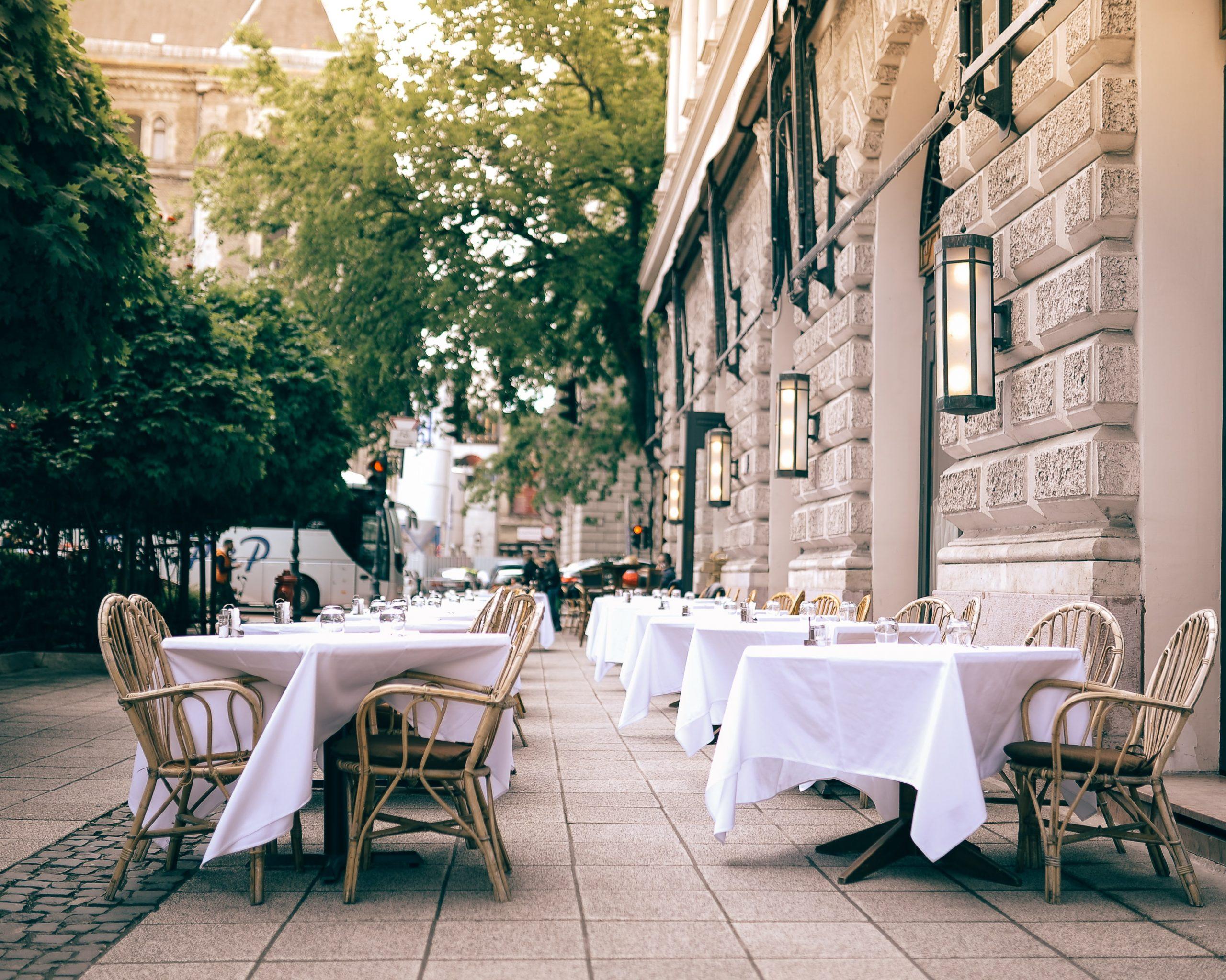 Na foto diversas mesas de um restante em uma calçada com árvores ao fundo.