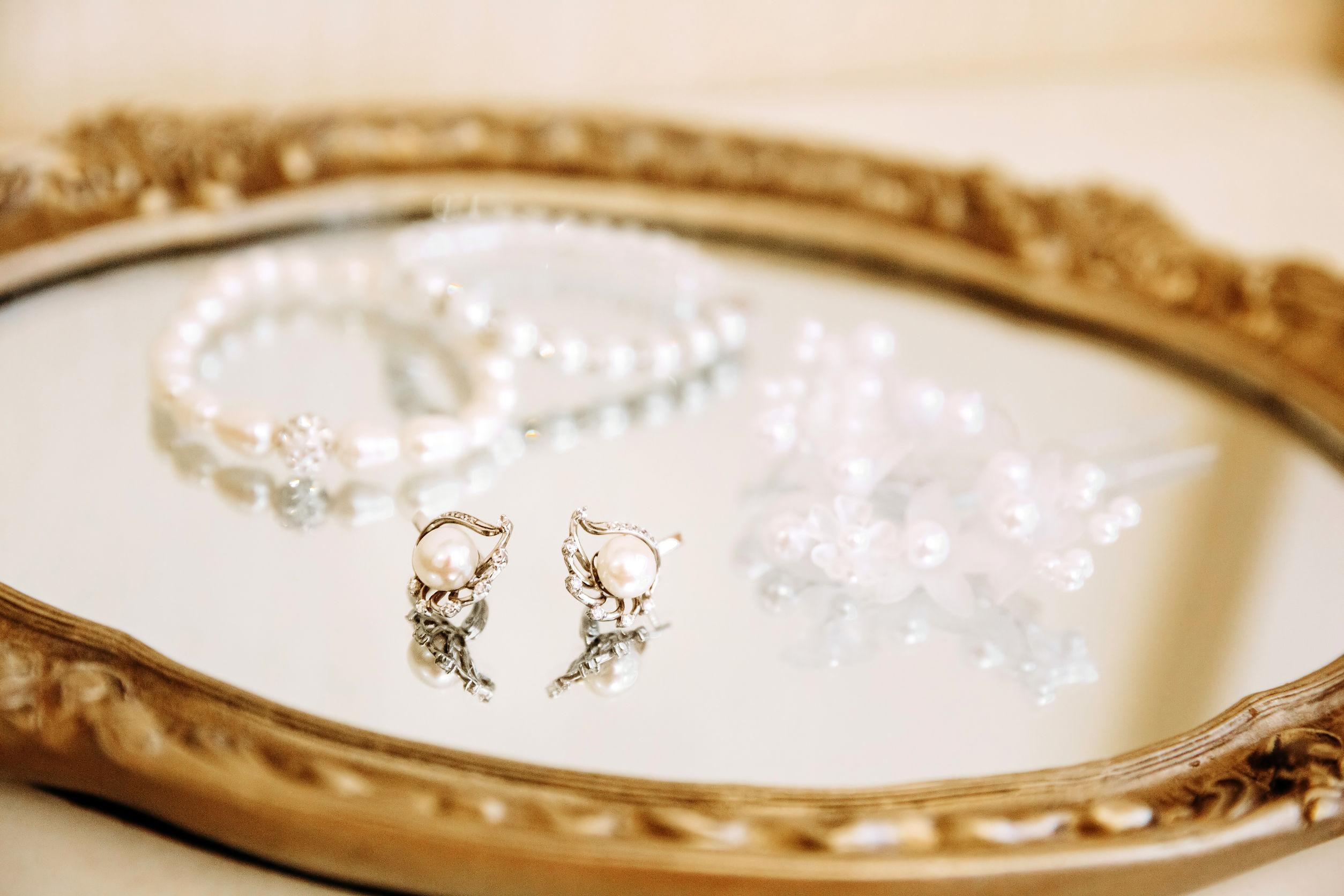 Na foto um par de brincos e pulseiras em cima de uma bandeja espelhada.