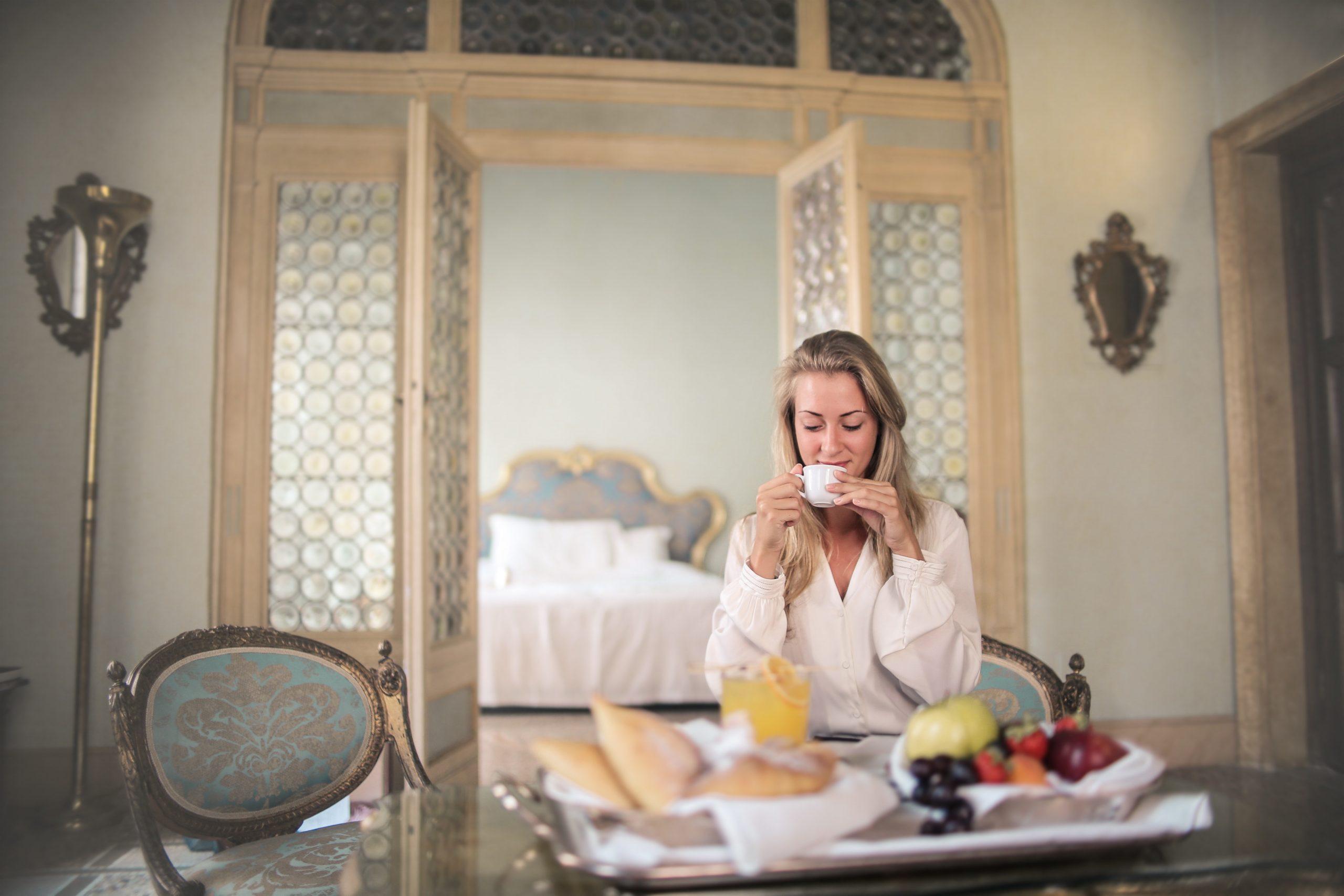 Na foto uma mulher sentada segunda uma xícara e na sua frente uma mesa com uma bandeja com frutas.