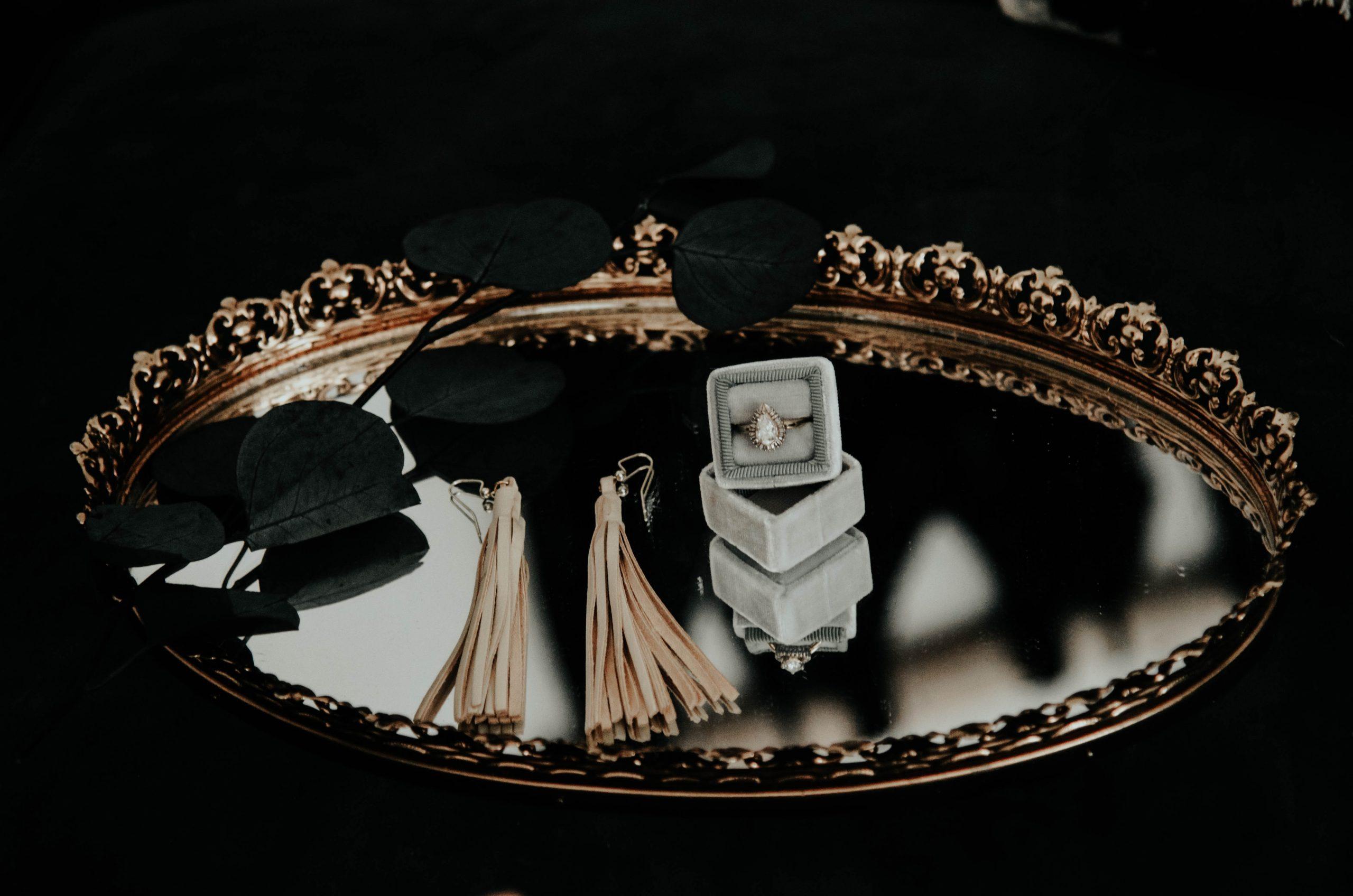 Na foto uma bandeja espelhada com dois brincos, uma flor e um anel em cima.