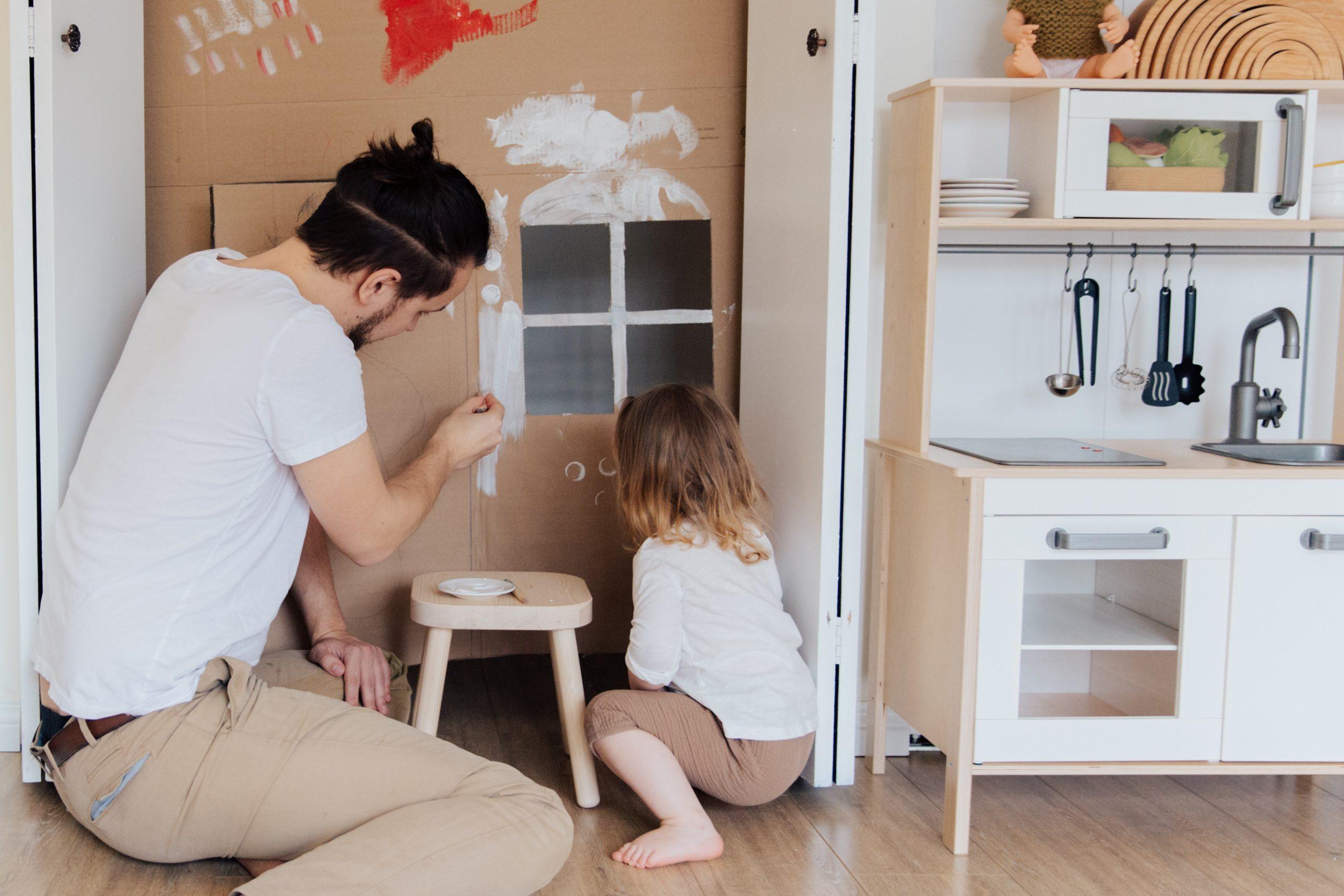 Imagem mostra pai e filha pintando juntos.