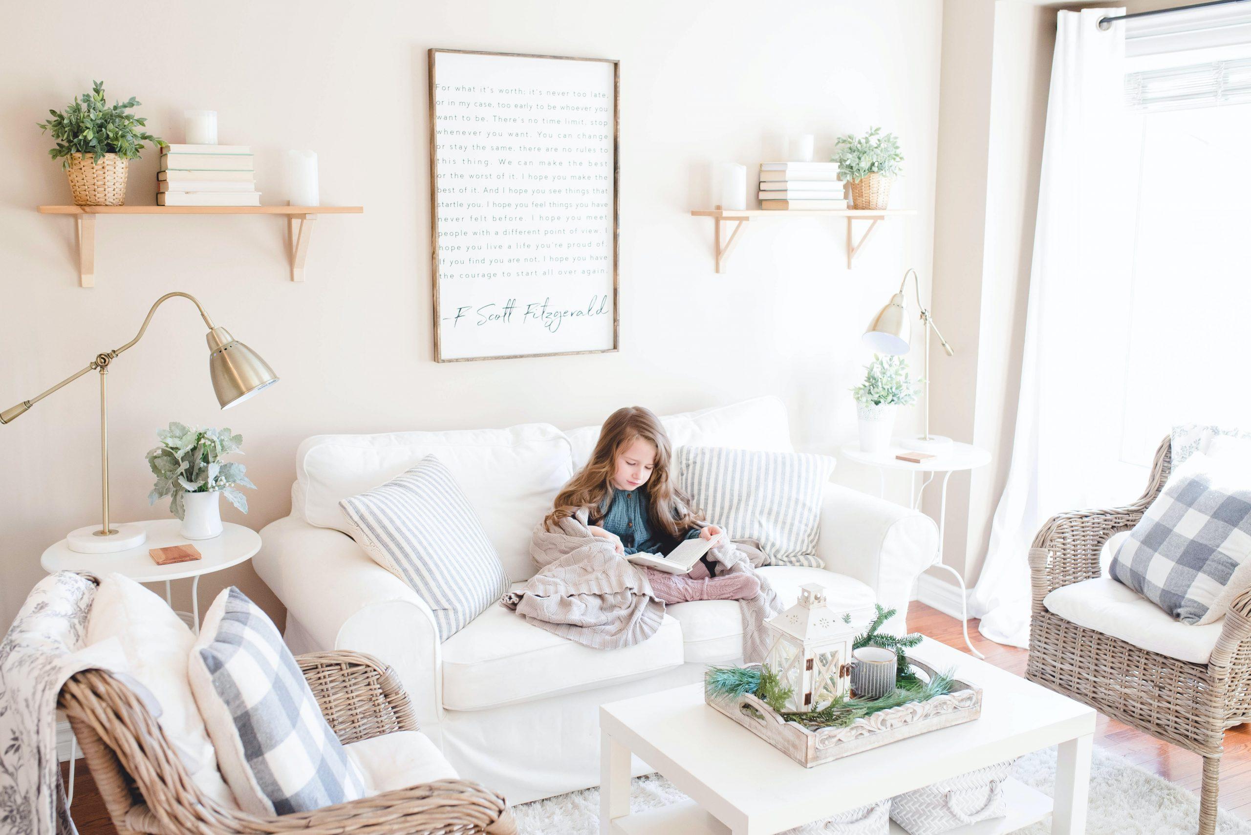 Na foto uma criança lendo em um sofá dentro de uma sala de estar.