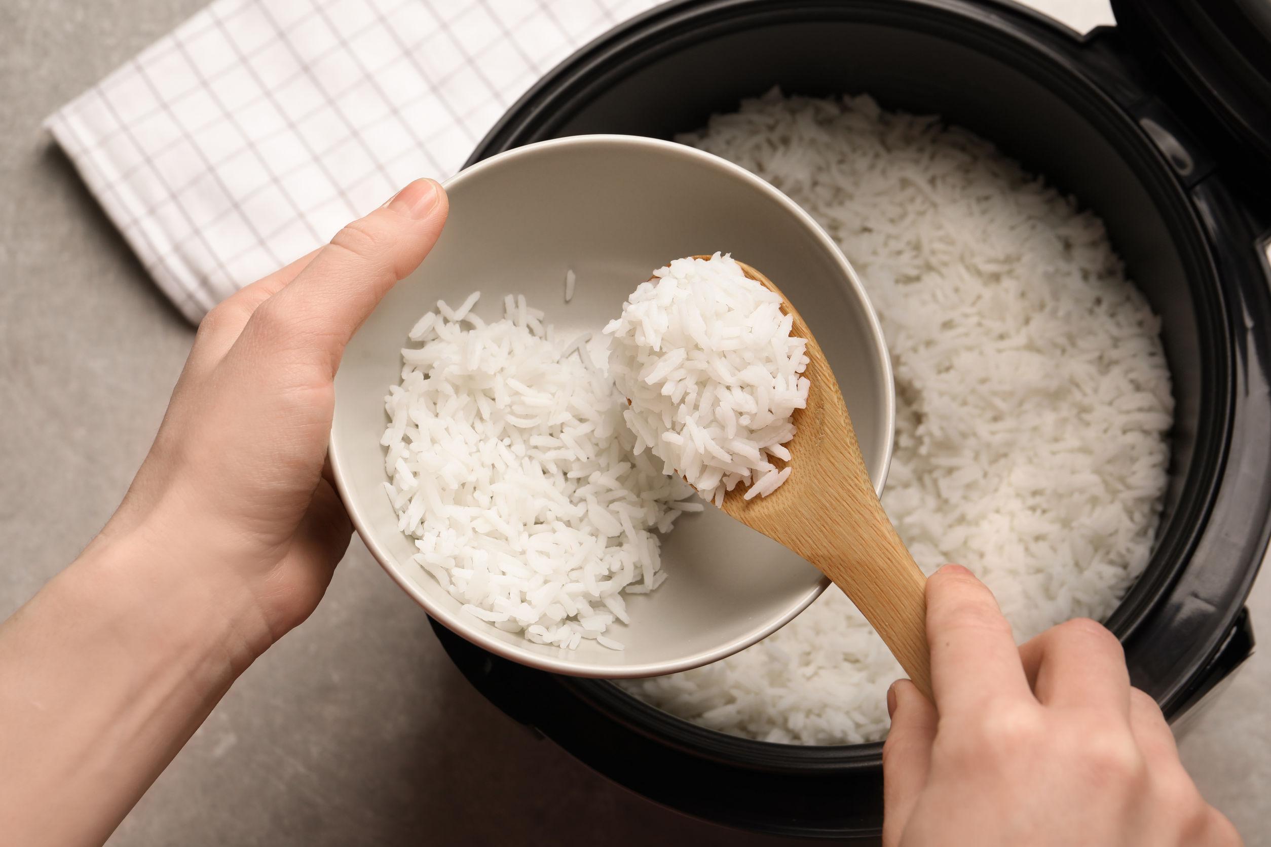 mulher servindo arroz feito na panela elétrica