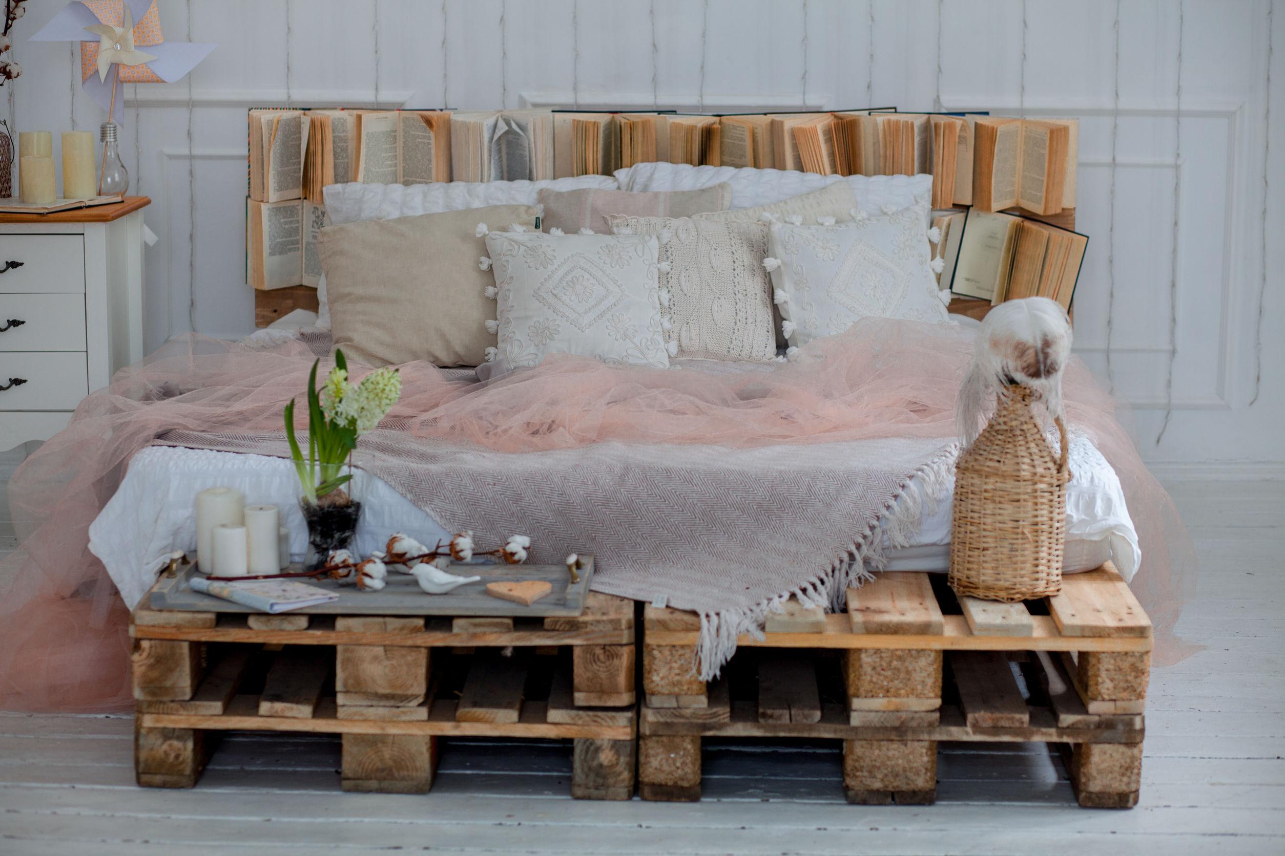 Na foto uma cama de casal feita com paletes cheia de almofadas.