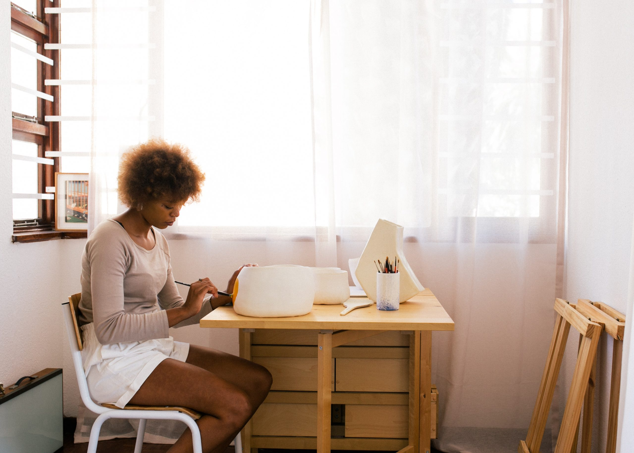 Na foto uma mulher sentada pintando uma tigela.