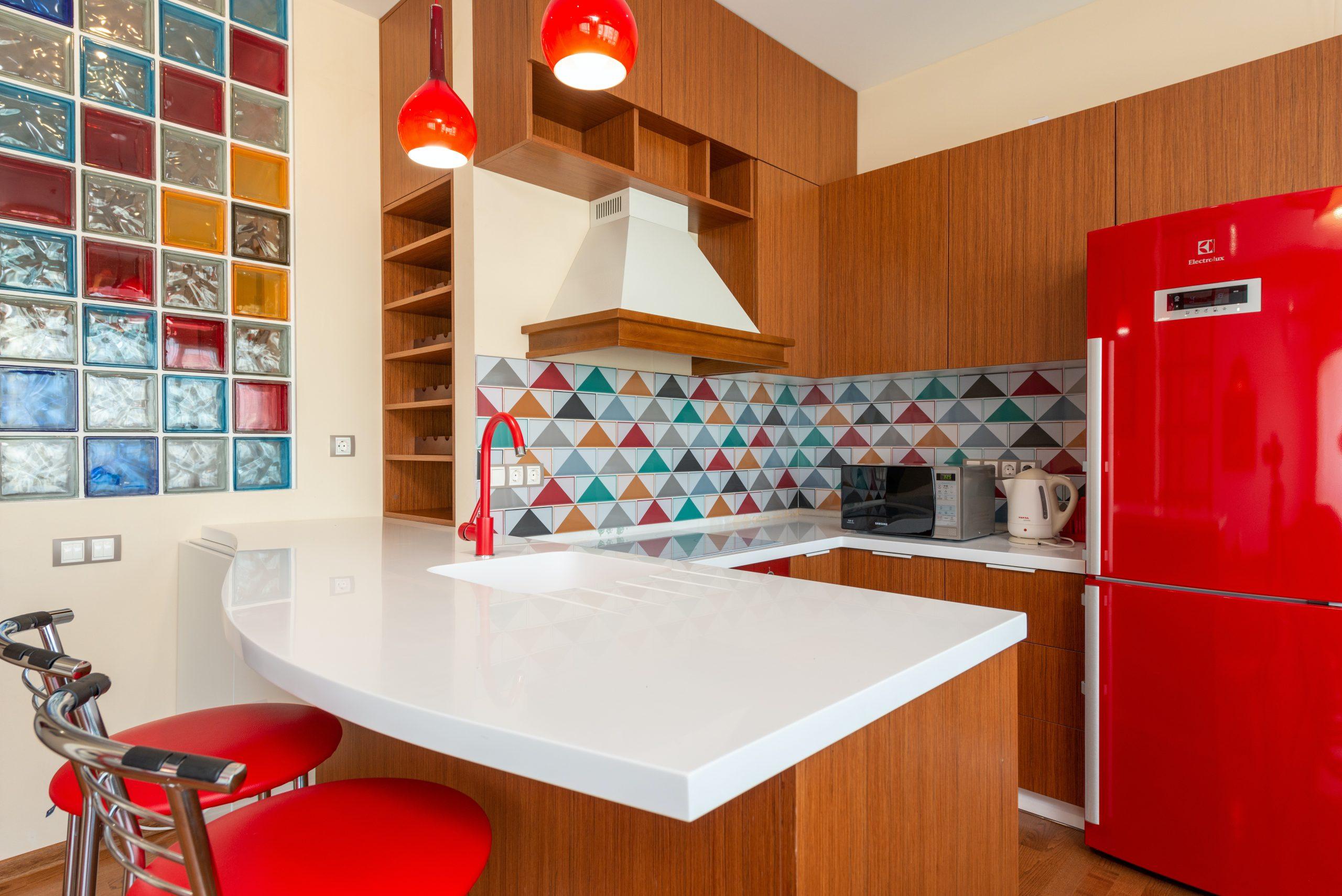 Na foto uma cozinha americana com decoração vermelha.