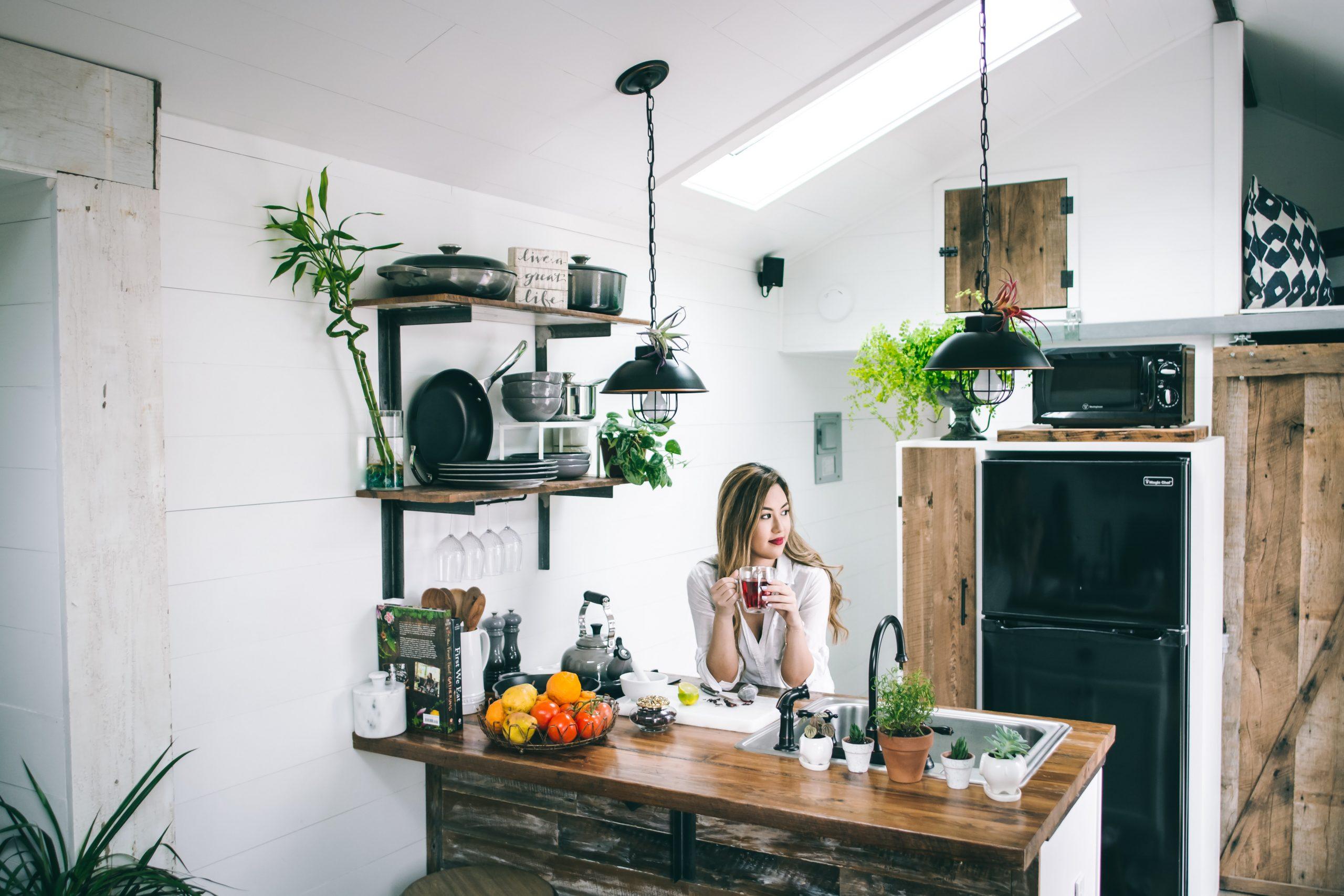 Na foto uma mulher encostada em uma bancada de cozinha segurando uma xícara na mão.