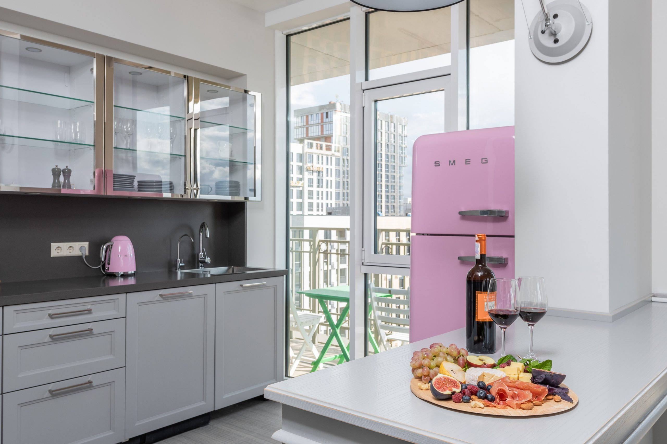 Na foto uma cozinha com geladeira rosa.