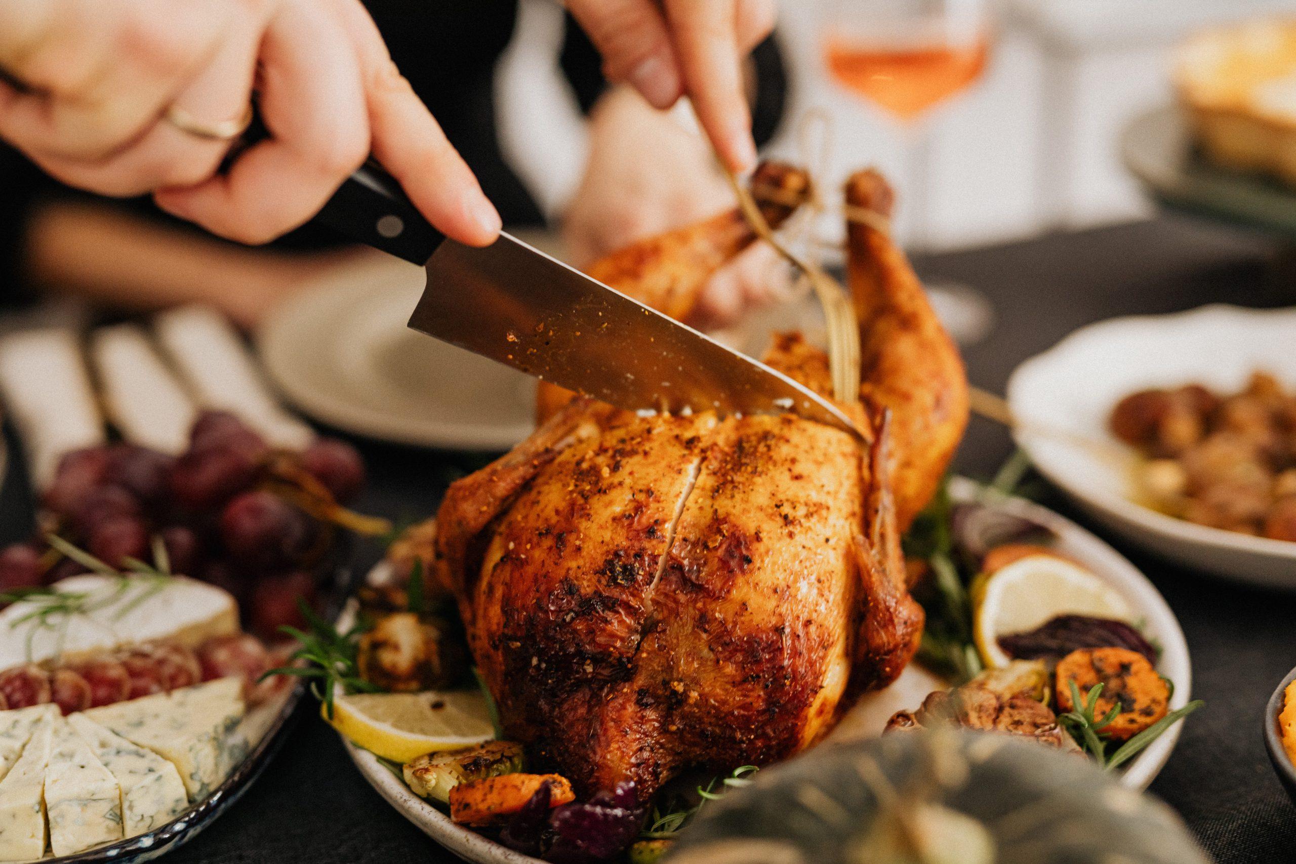 Imagem mostra mão cortando frango assado.