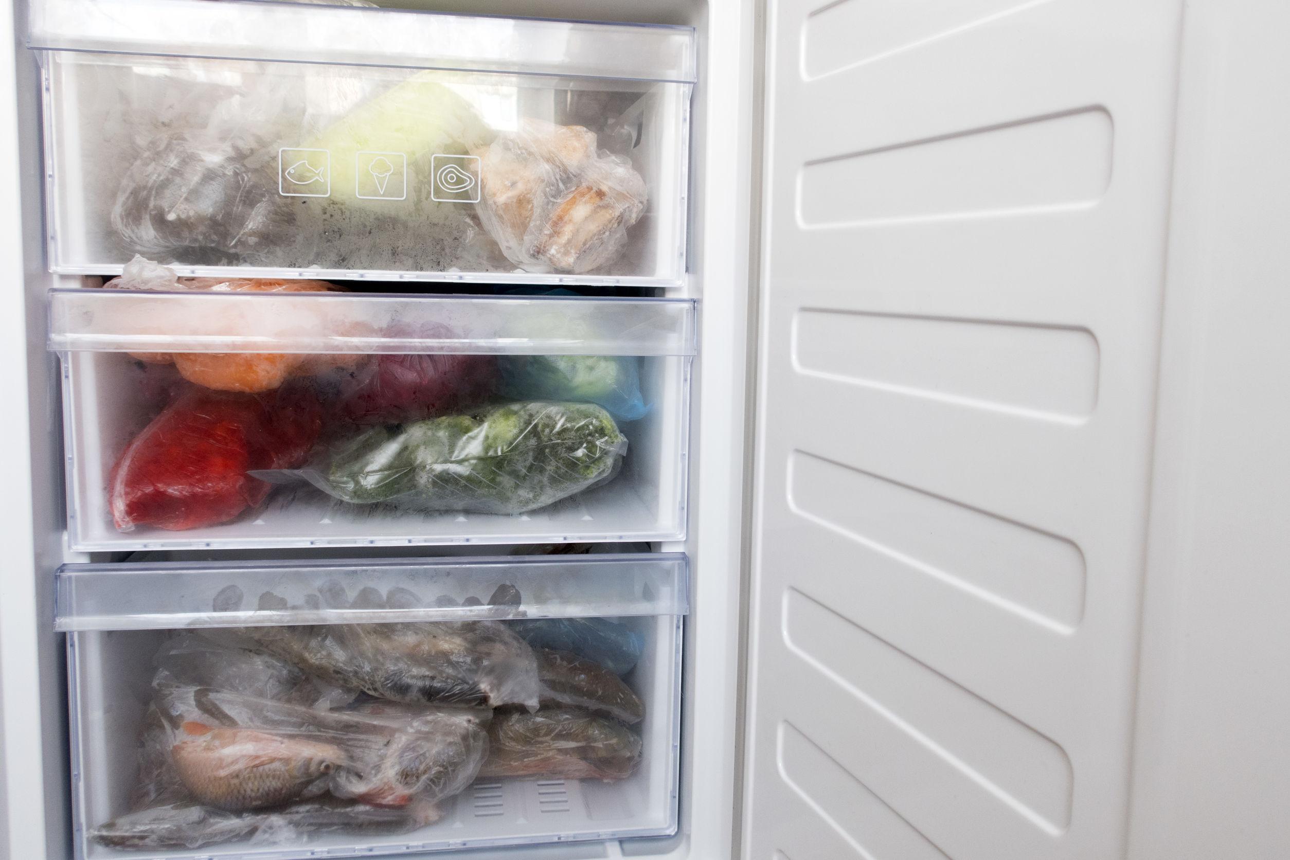 Freezer vertical aberto com alimentos congelados no interior
