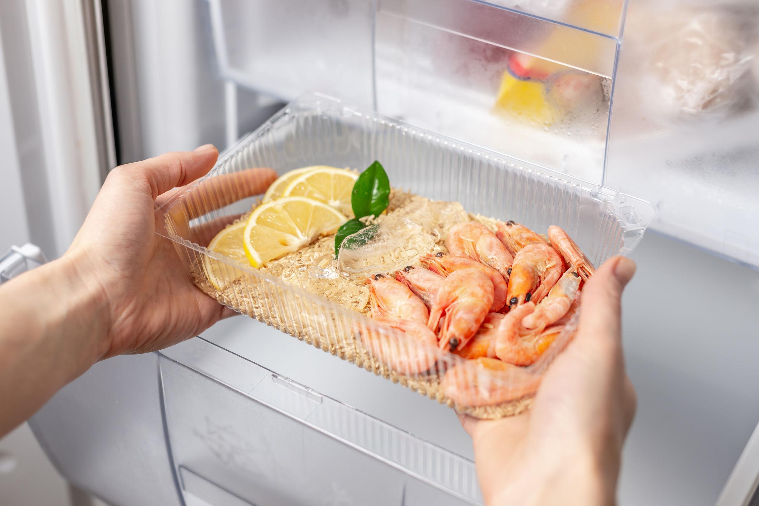 Mulher com refeição pronta para ser congelada em frente a um freezer vertical