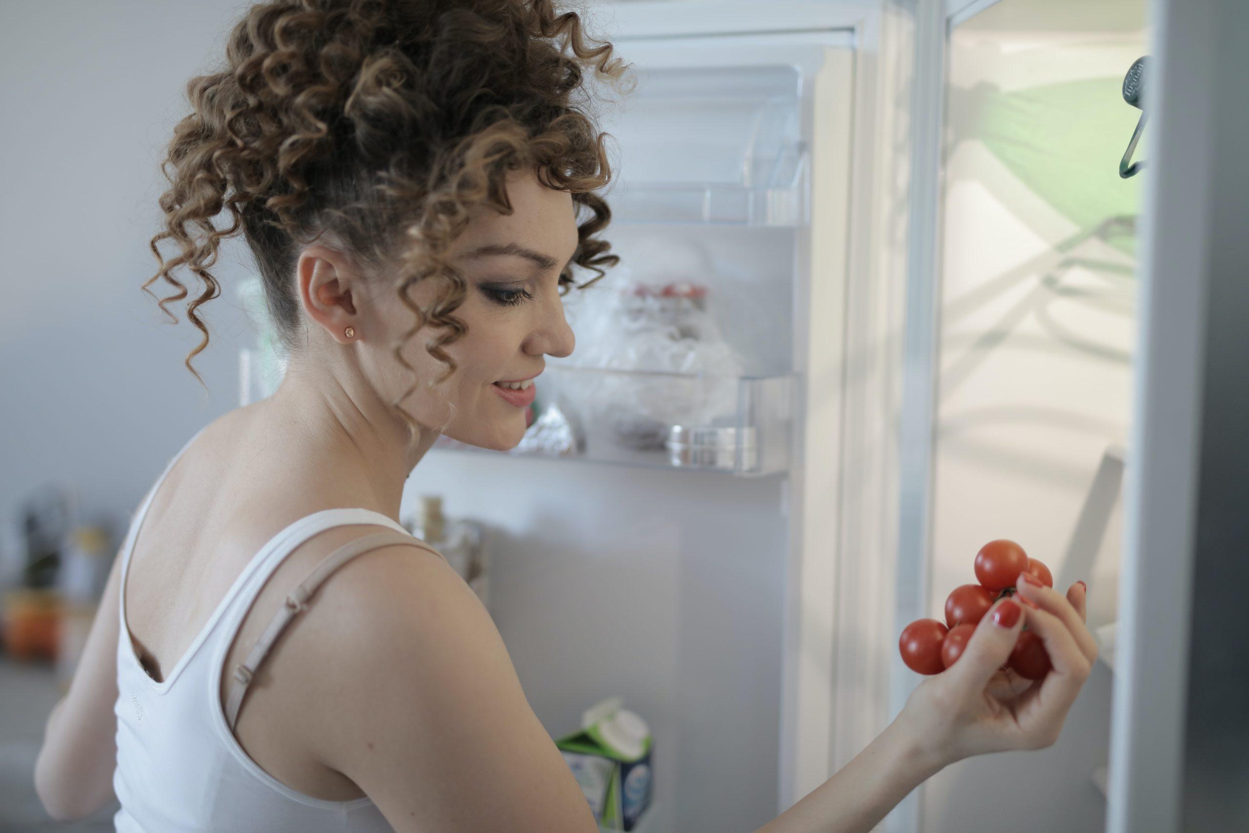 Imagem de uma mulher pegando tomates na geladeira.