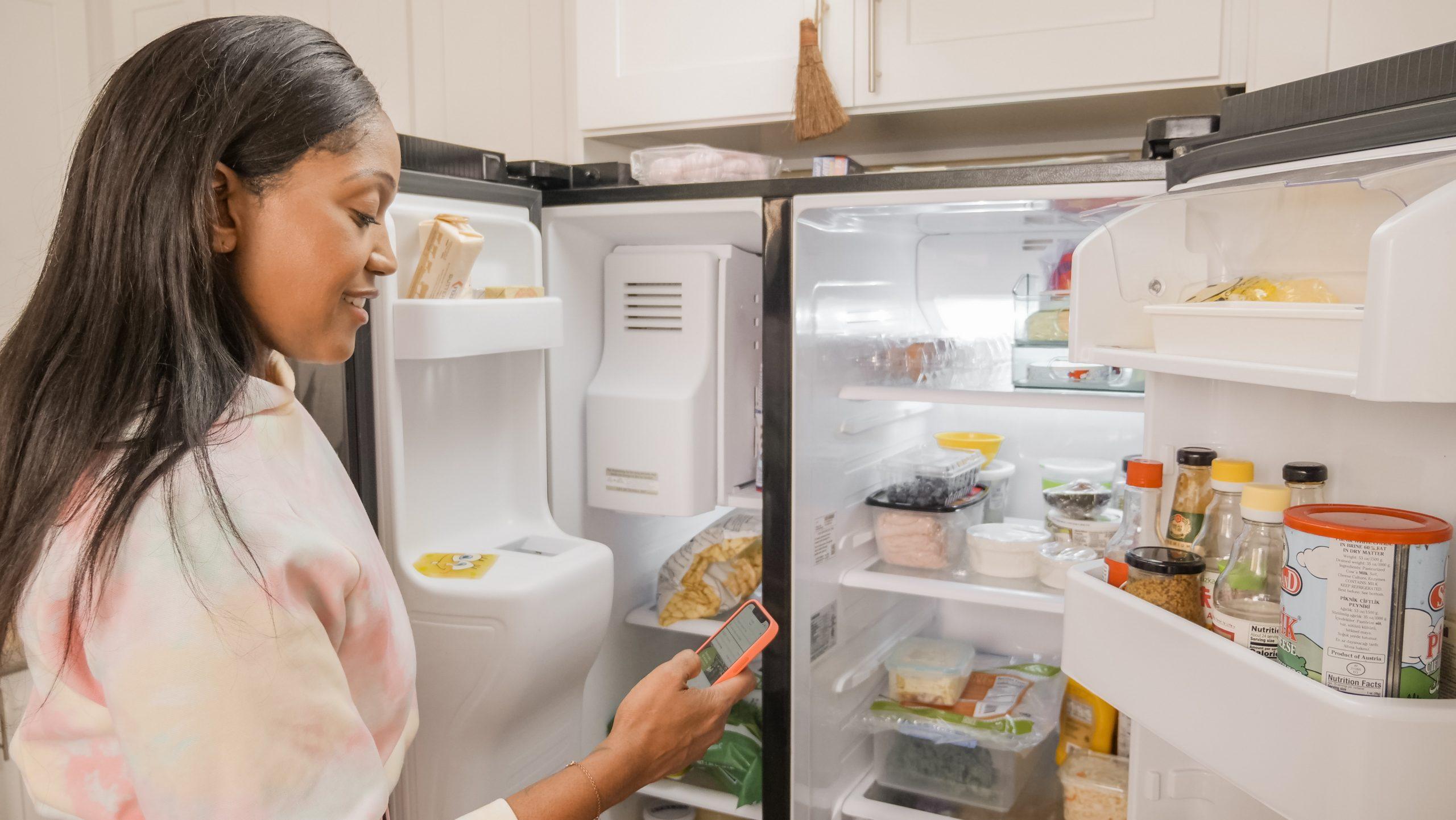 Imagem de uma mulher utilizando o smartphone em frente à geladeira.