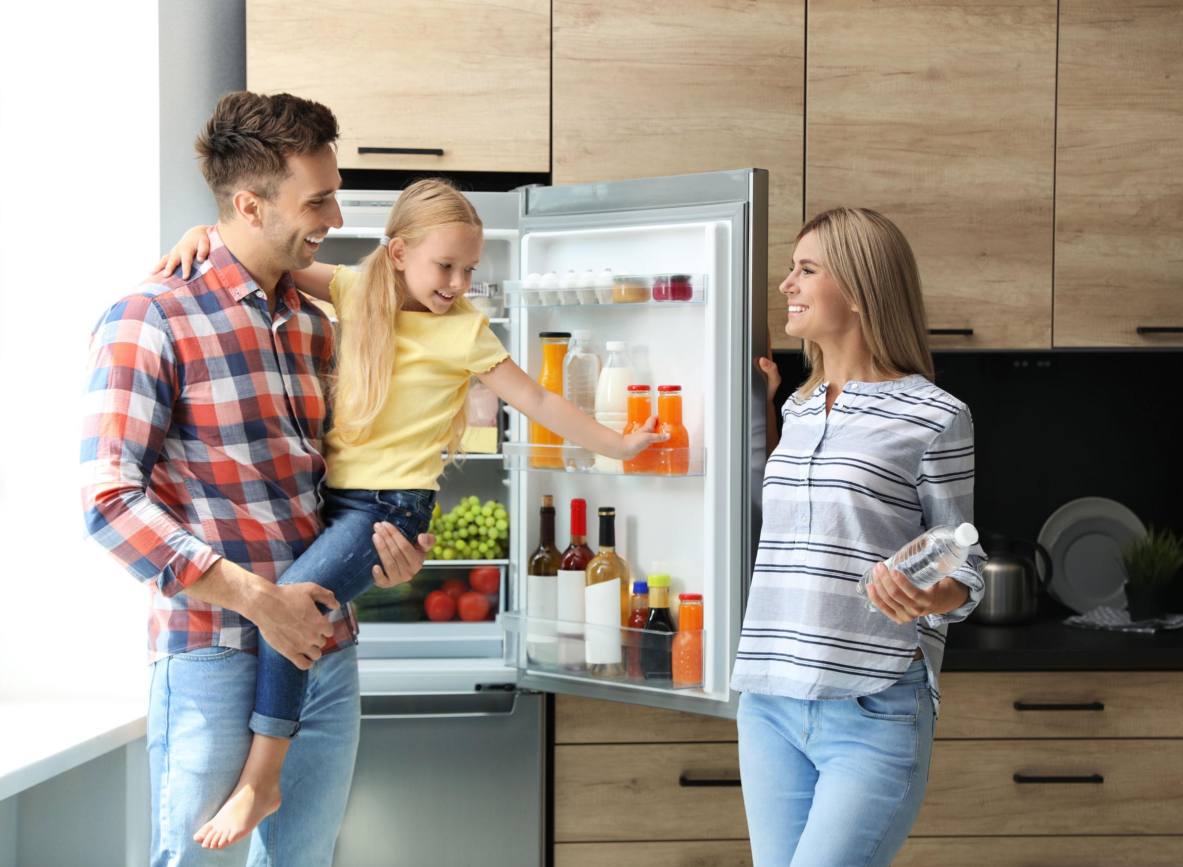 Família feliz em frente a uma geladeira aberta cheia de comida.