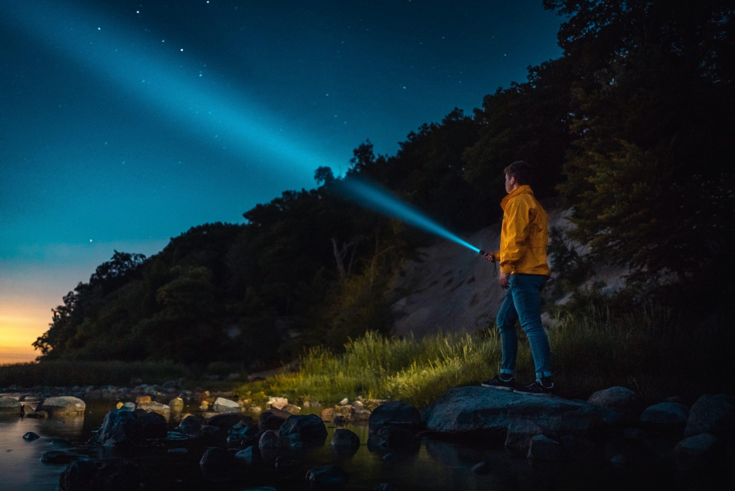 Na foto um homem apontando uma lanterna para cima.