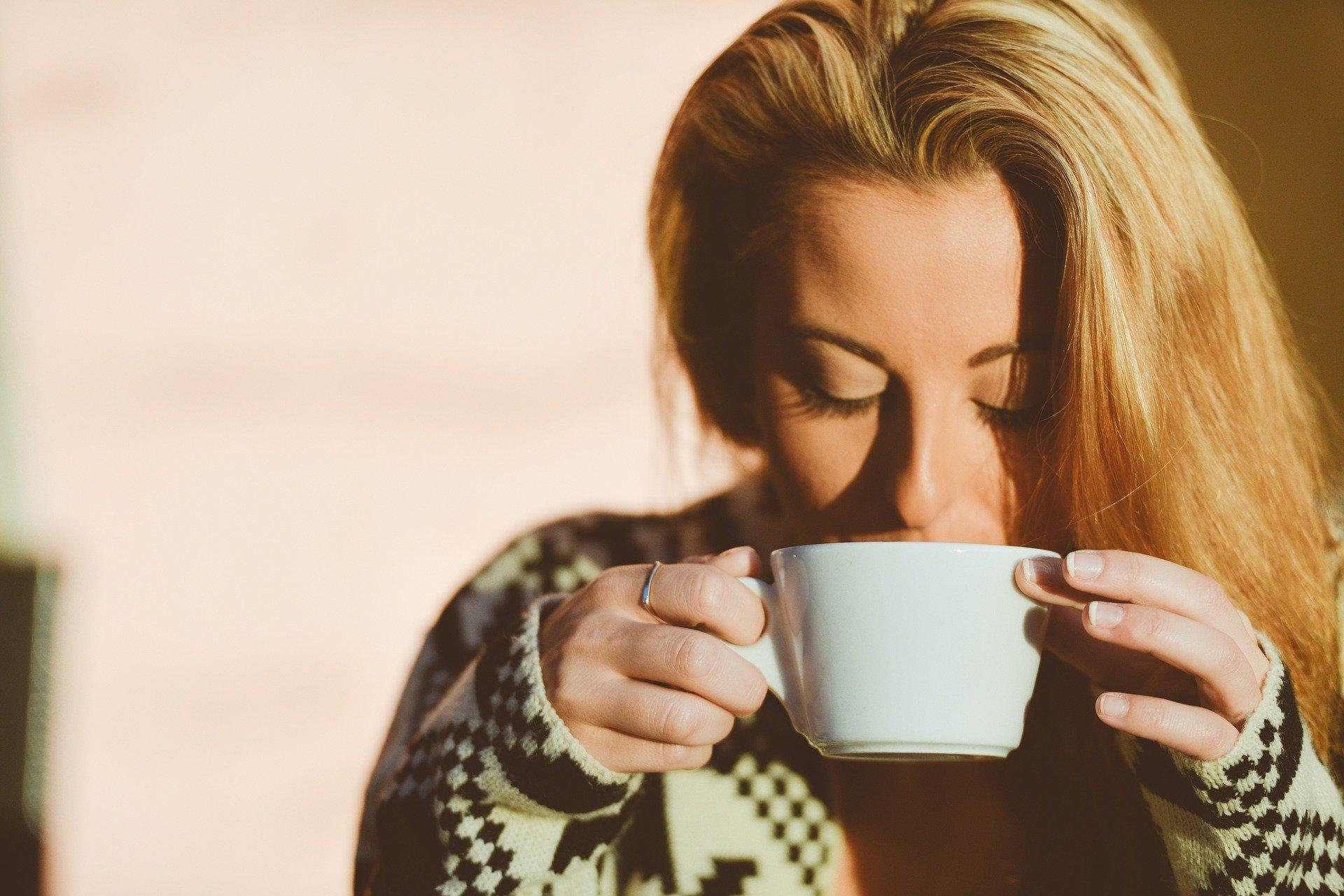 Mulher bebendo café na xícara.