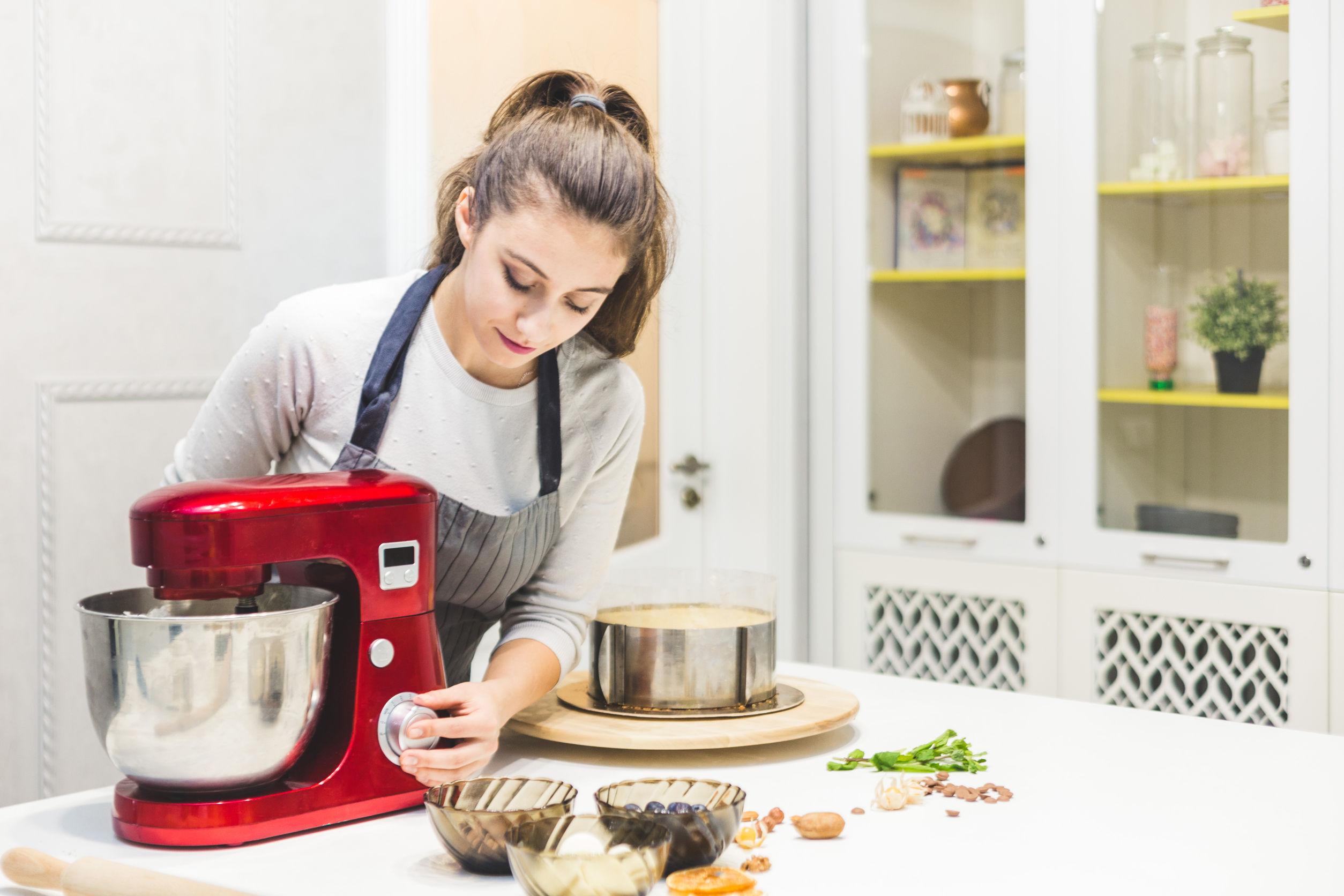 mulher jovem preparando bolo com uma batedeira planetária