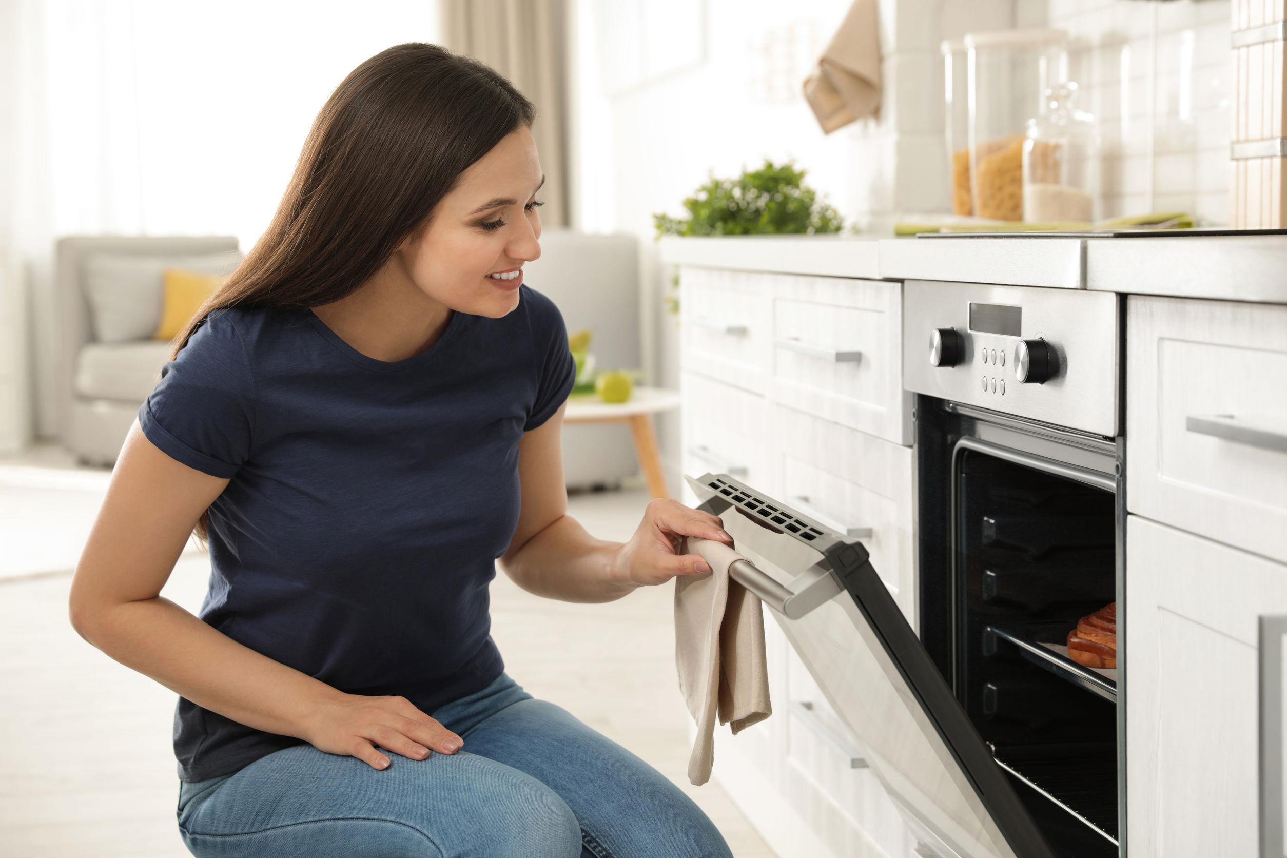 Na foto uma mulher abrindo um forno com uma pizza dentro