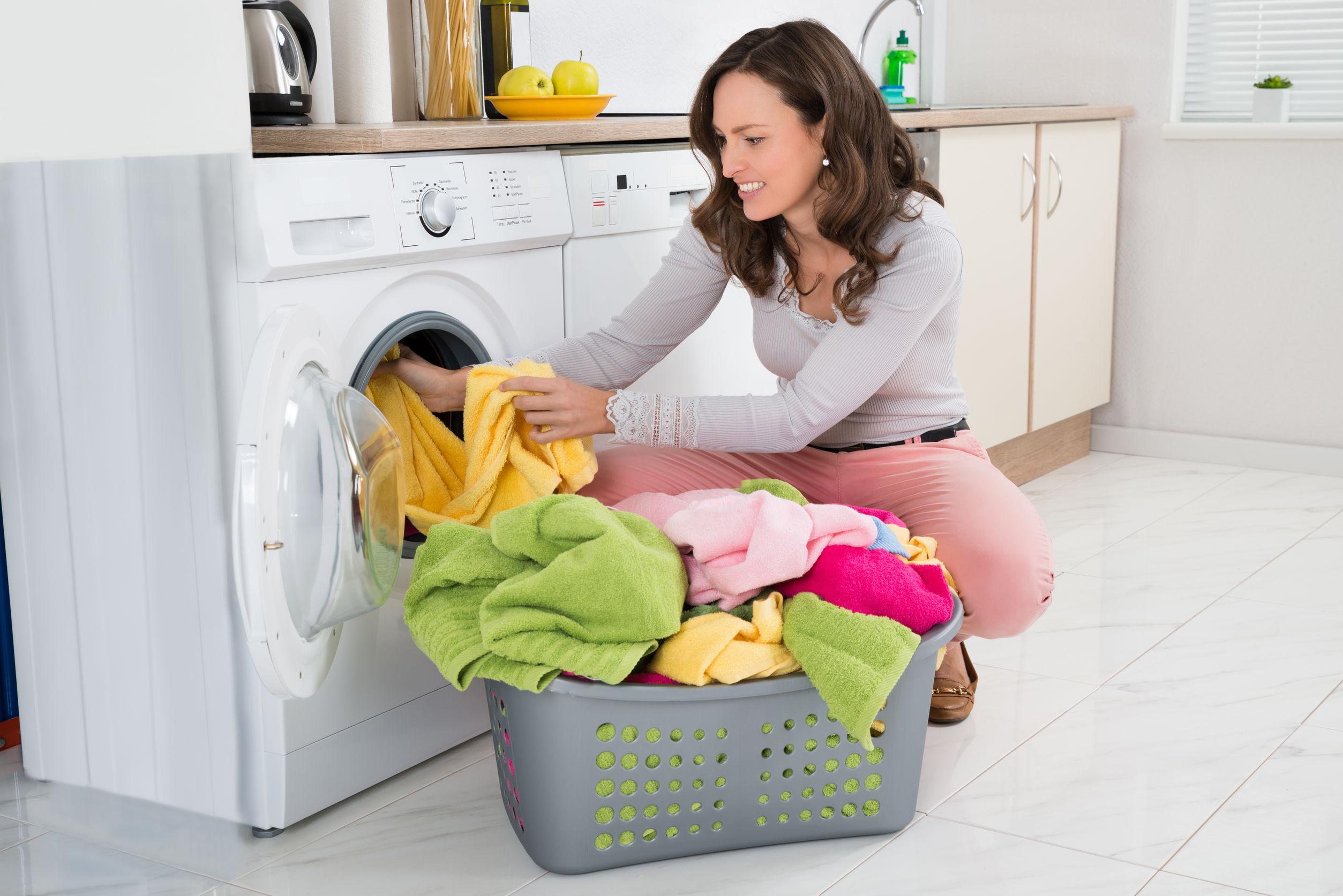 mulher colocando as roupas em uma lava e seca