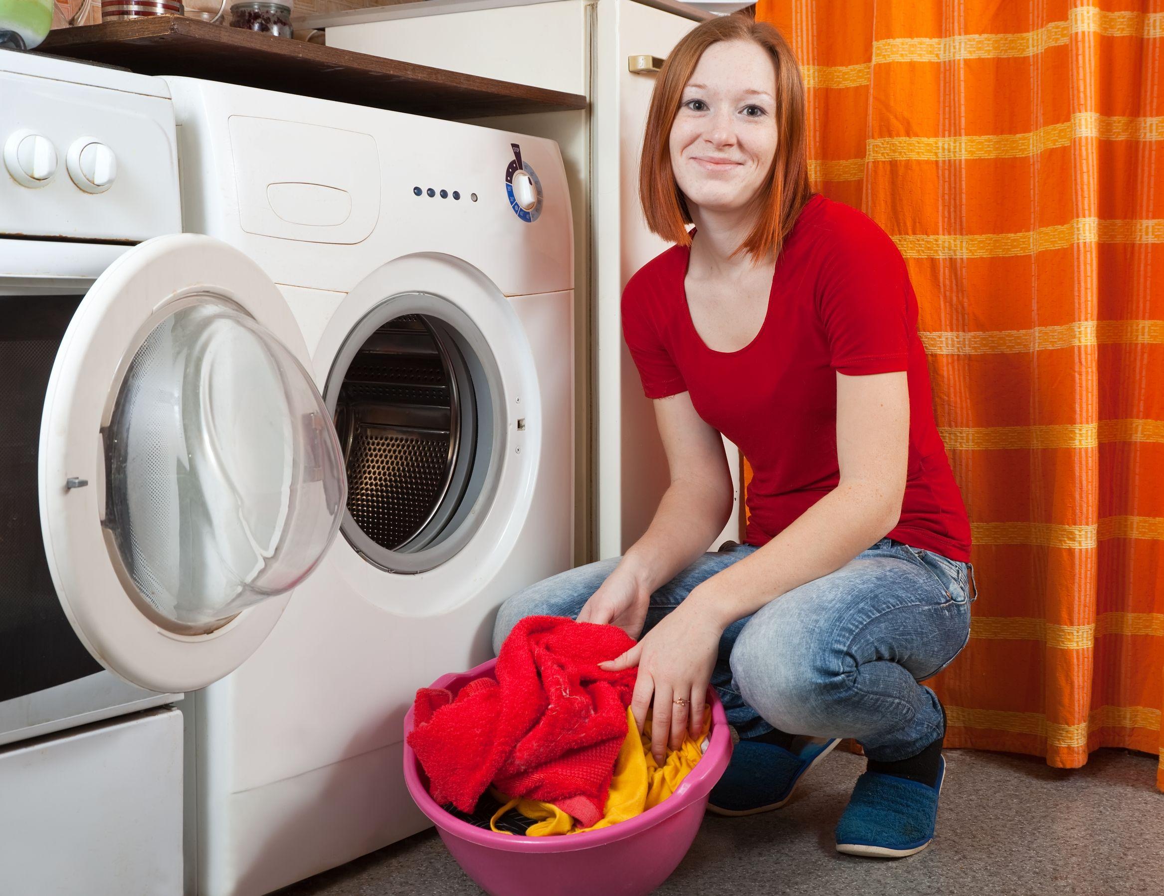 mulher colocando a roupa em uma lava e seca na lavanderia