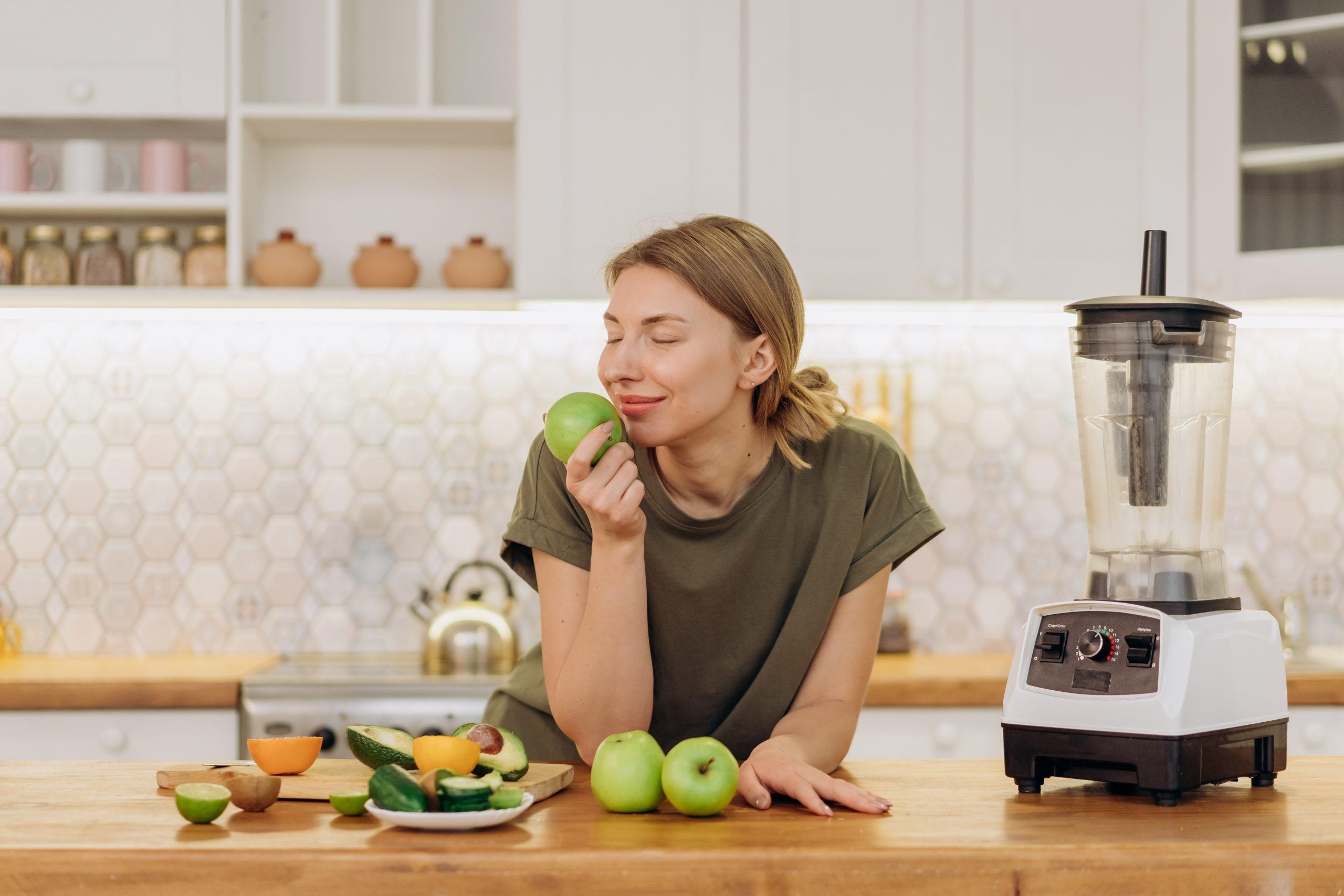 Imagem de uma mulher cheirando uma maçã.