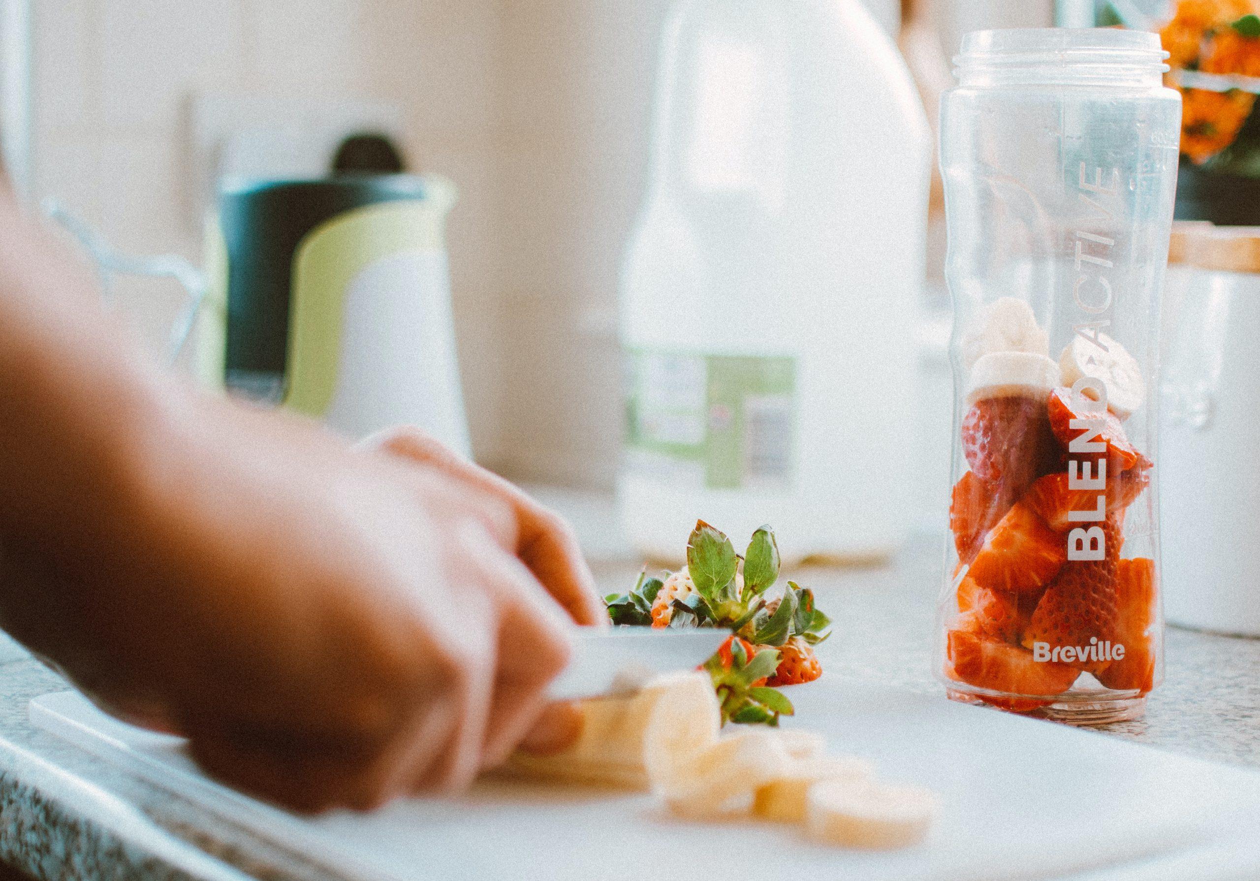 Imagem de uma pessoa cortando frutas para fazer uma vitamina.