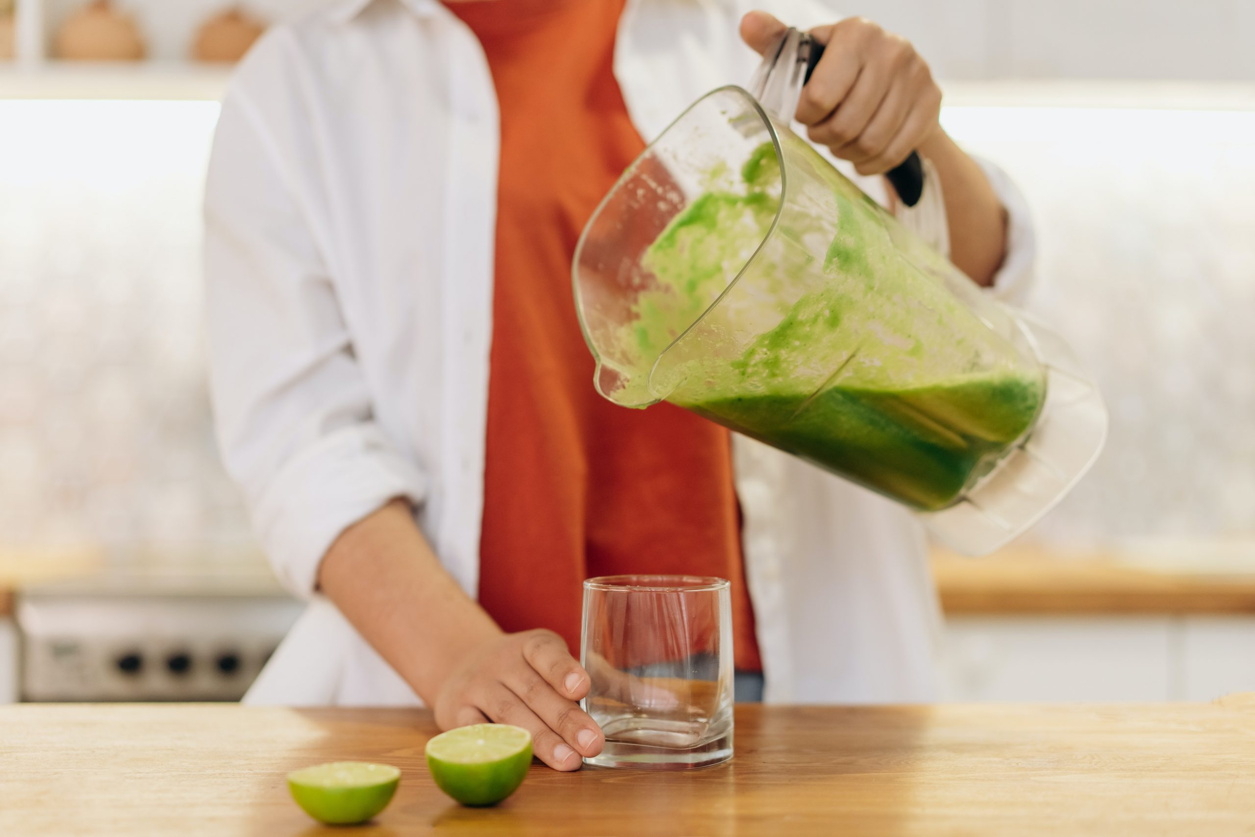 Imagem de uma mulher despejando um suco no copo.