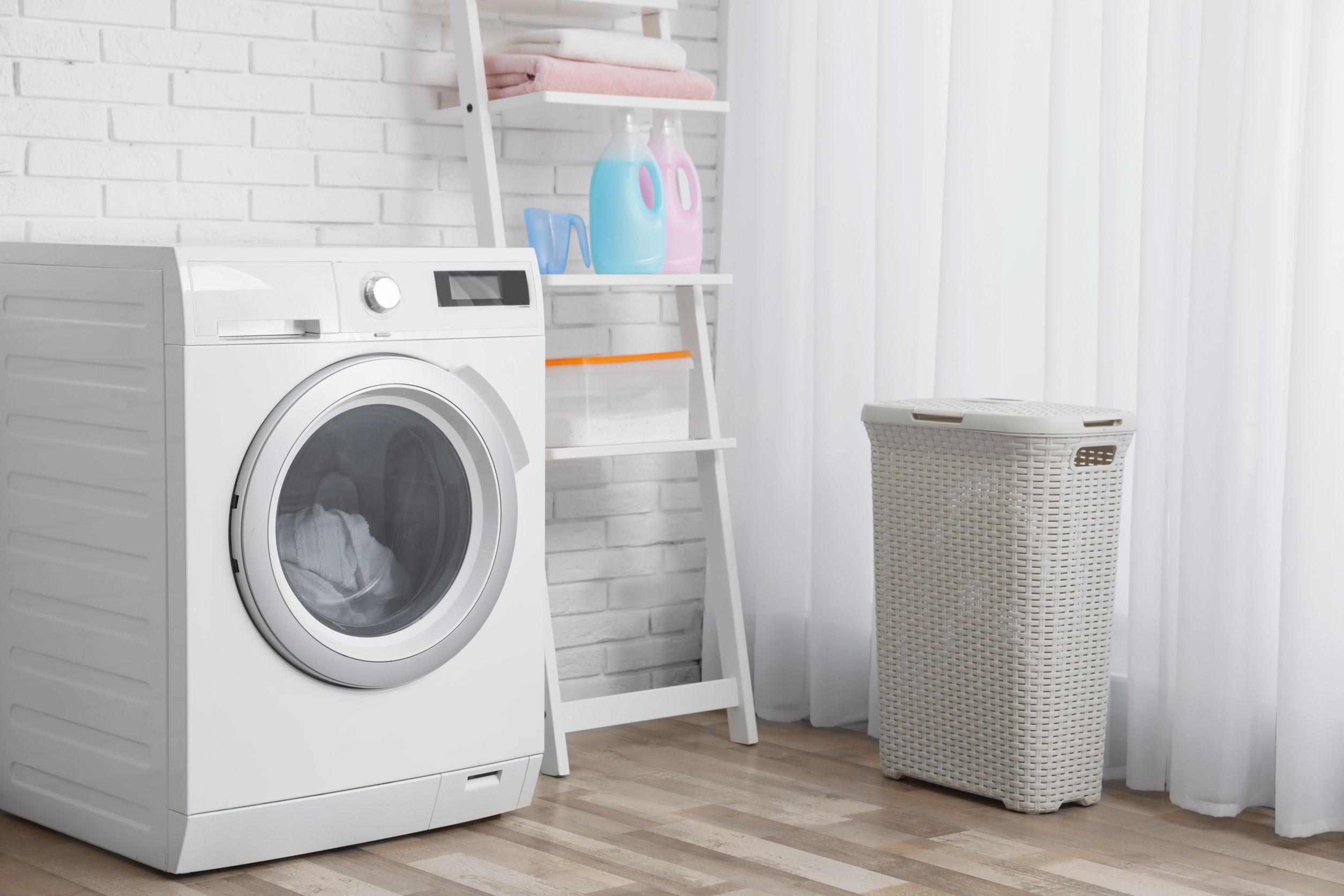 máquina de lavar ao lado de uma prateleira na lavanderia