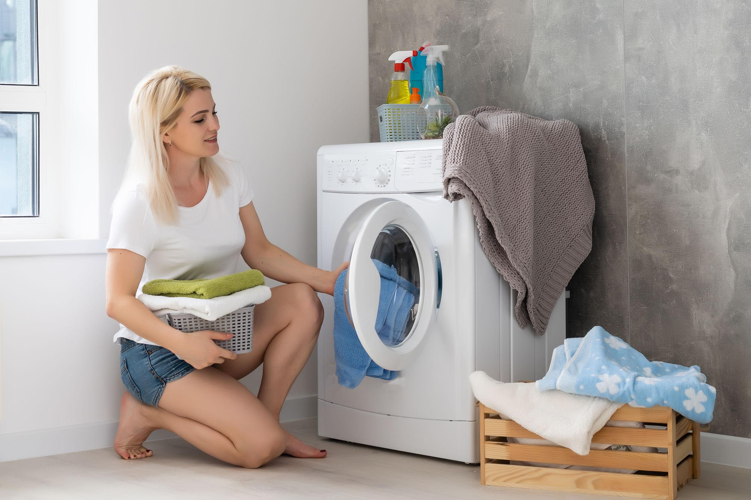 mulher jovem de toalha colocando roupas na máquina de lavar