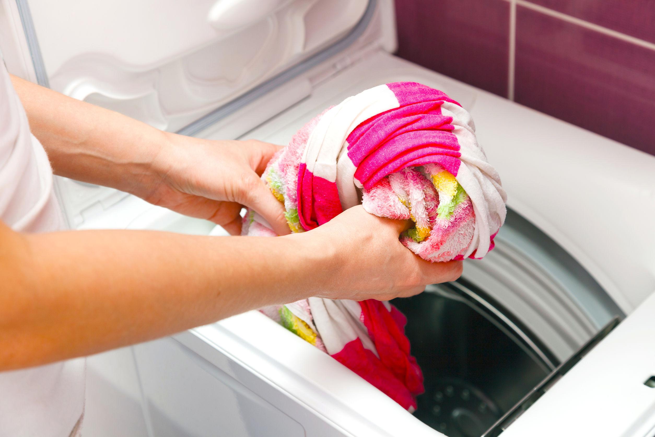 Roupas coloridas sendo colocadas na máquina de lavar