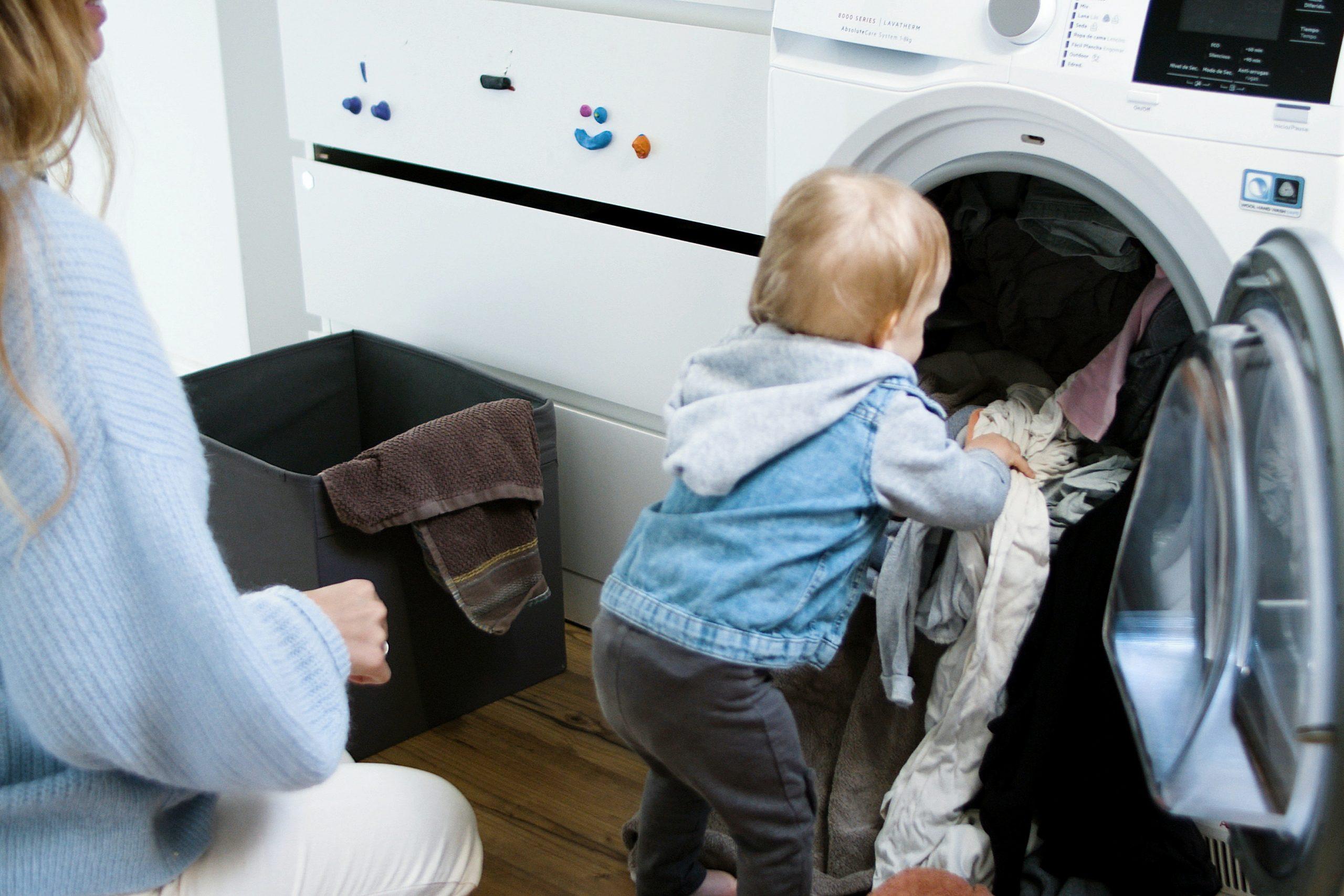 Menino pequeno colocando roupas na máquina de lavar com a mãe ao lado