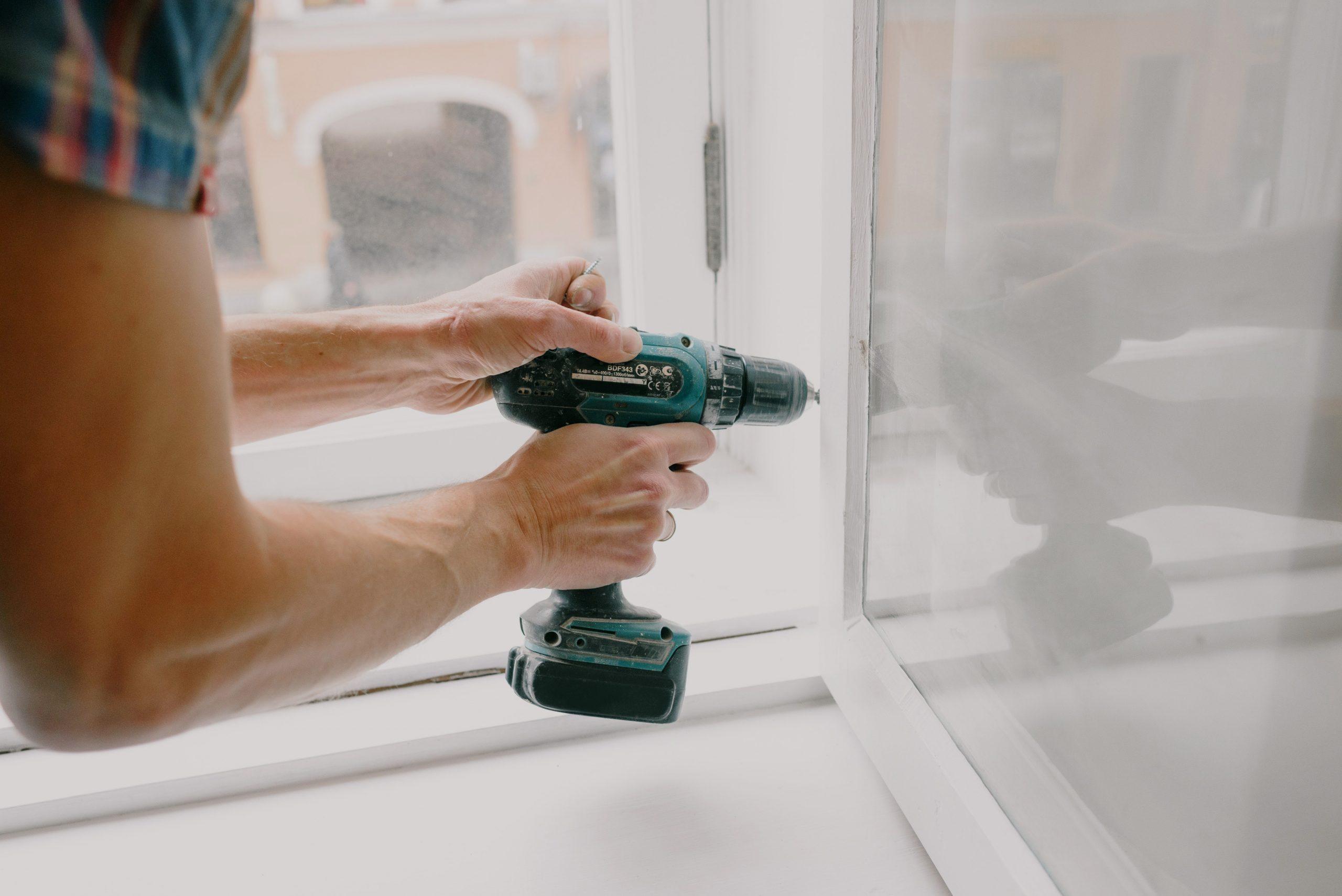 Imagem mostra uma pessoa usando uma parafusadeira em uma janela.
