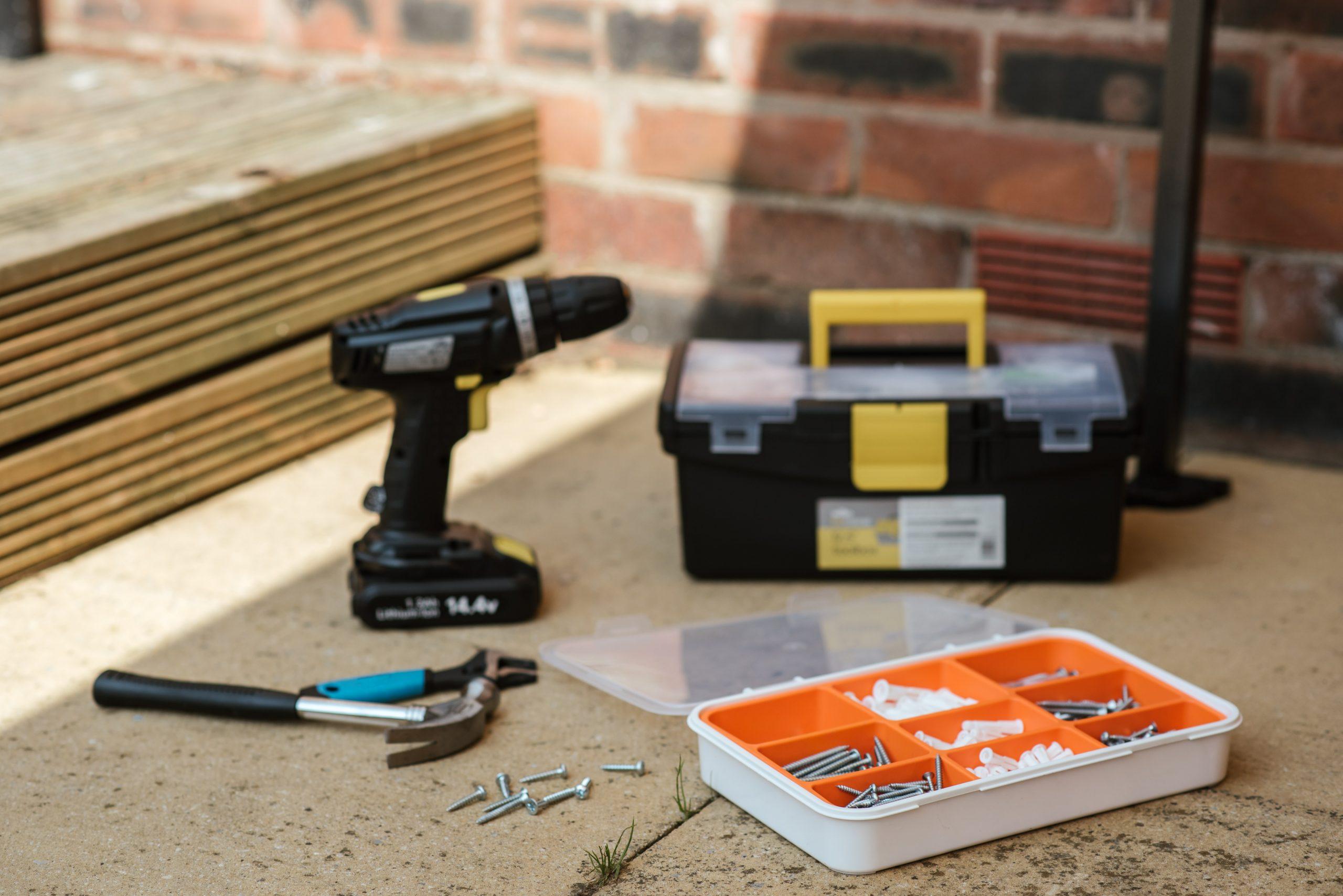 Imagem mostra uma parafusadeira junto a uma caixa de ferramentas e vários parafusos.