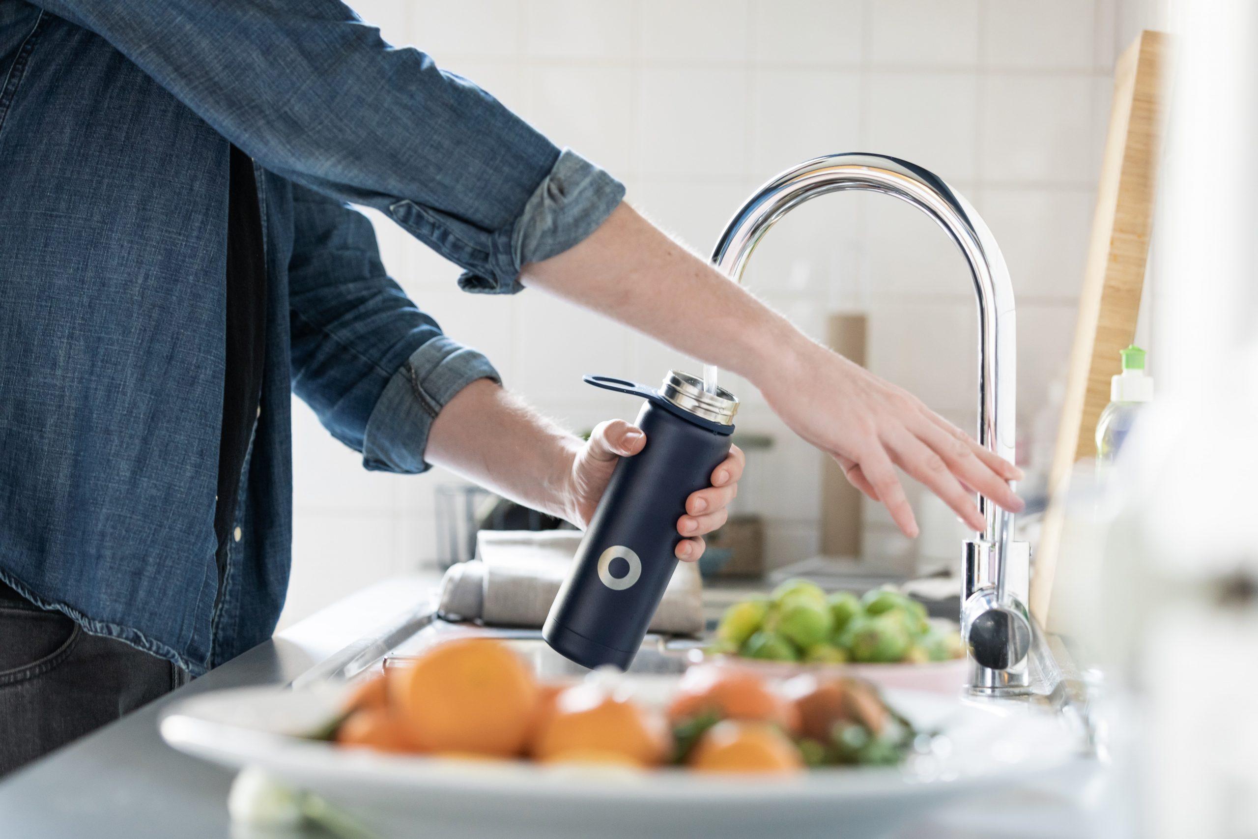 Pessoa pegando água da torneira.