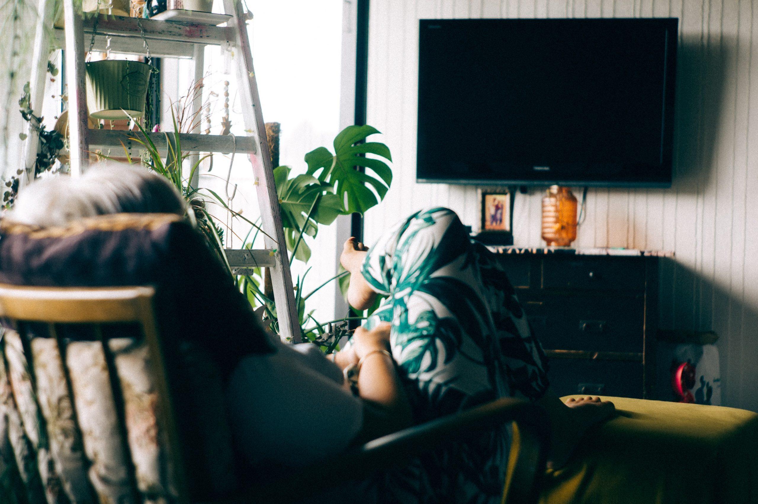 Na foto uma mulher sentada em uma cadeira em frente a uma televisão.