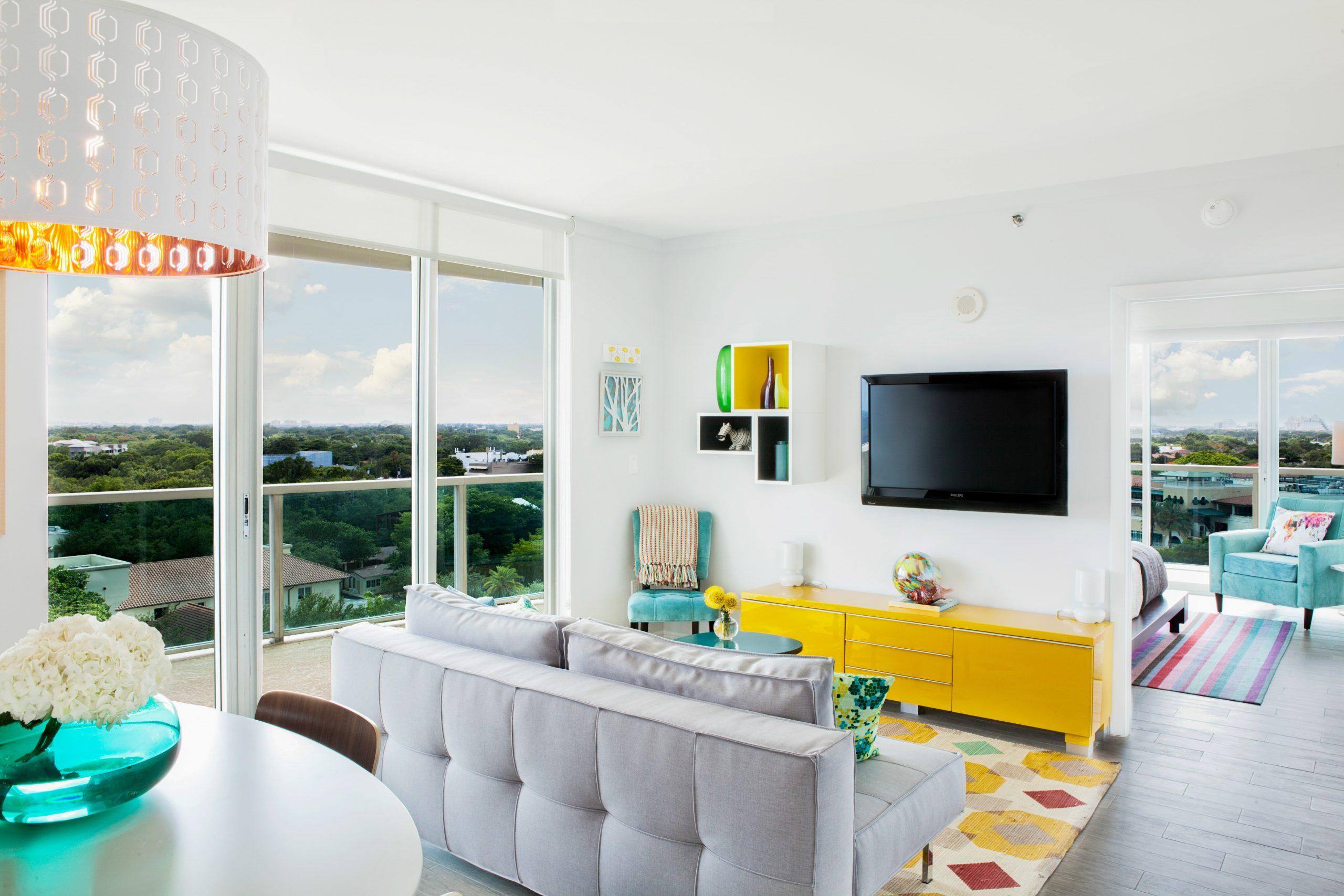 Na foto uma sala de estar com uma janela grande e um móvel amarelo.