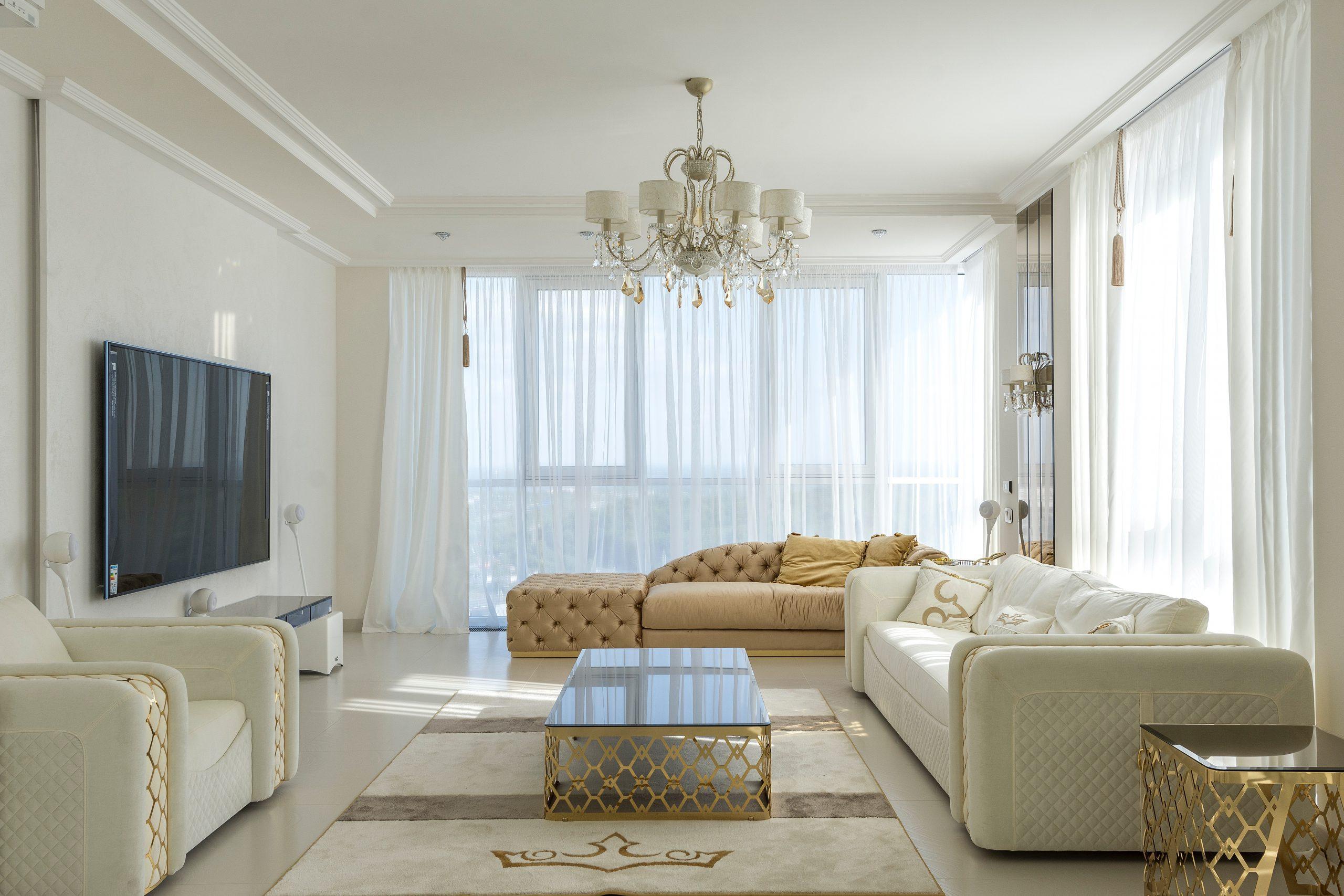 Na foto uma sala de estar com móveis beges e brancos e uma TV na parede.