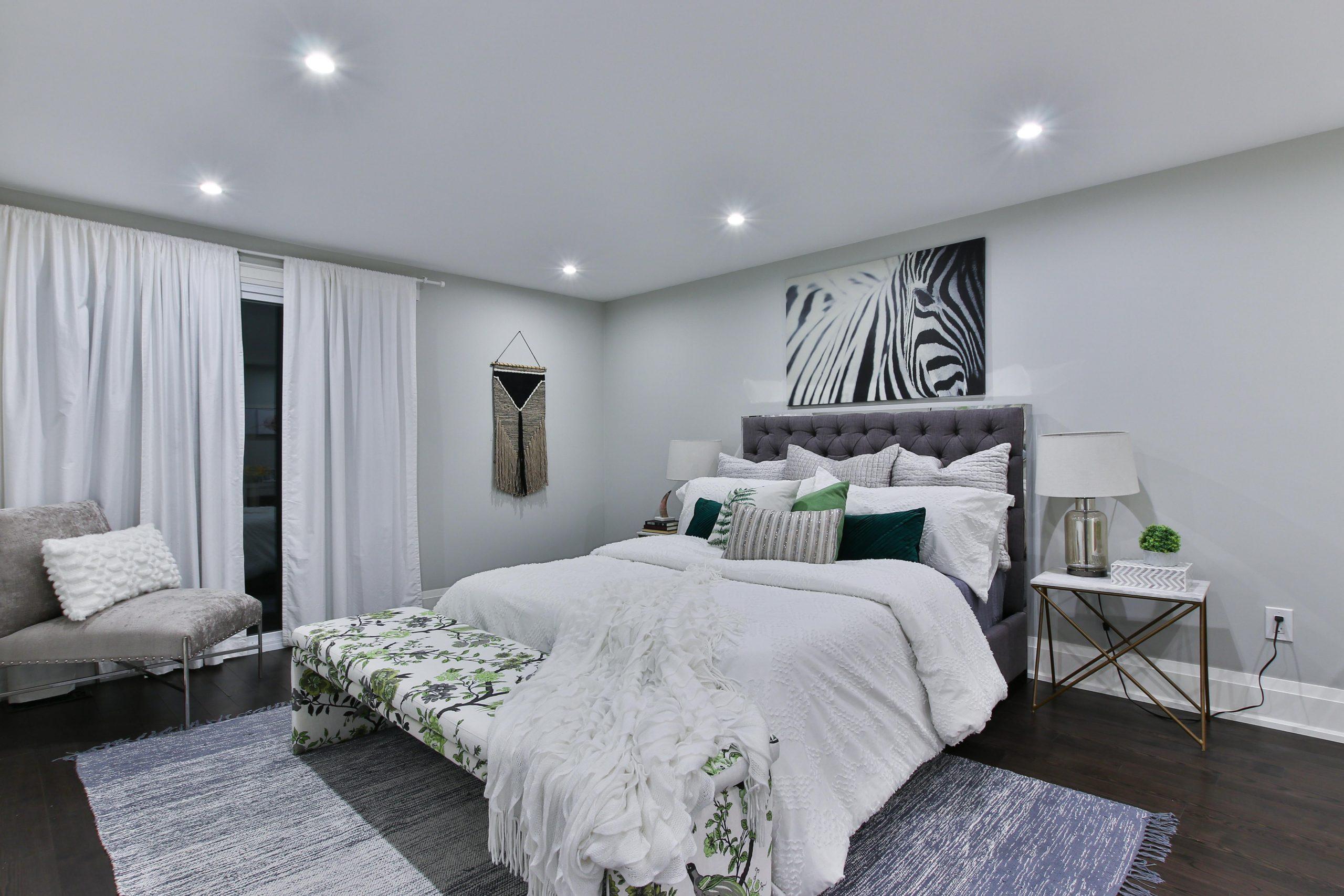 Na foto um quarto de casal com decoração em cinza e branco.