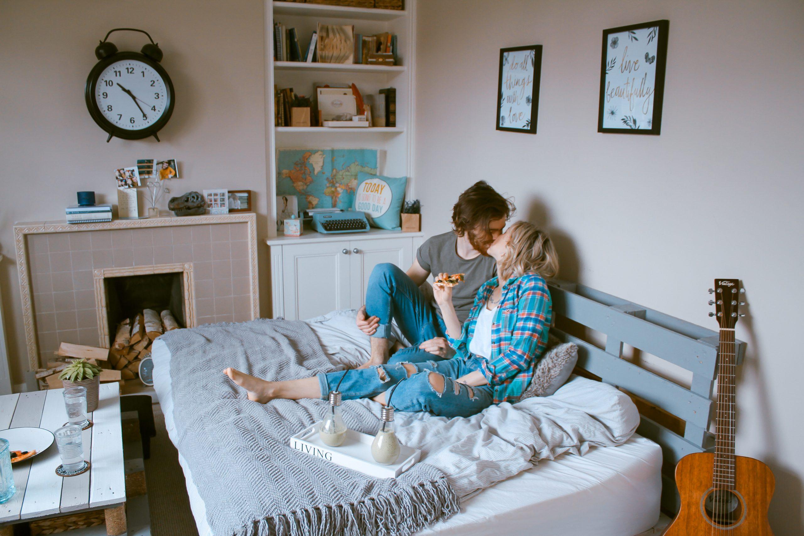 Na foto um casal deitado na cama se beijando.