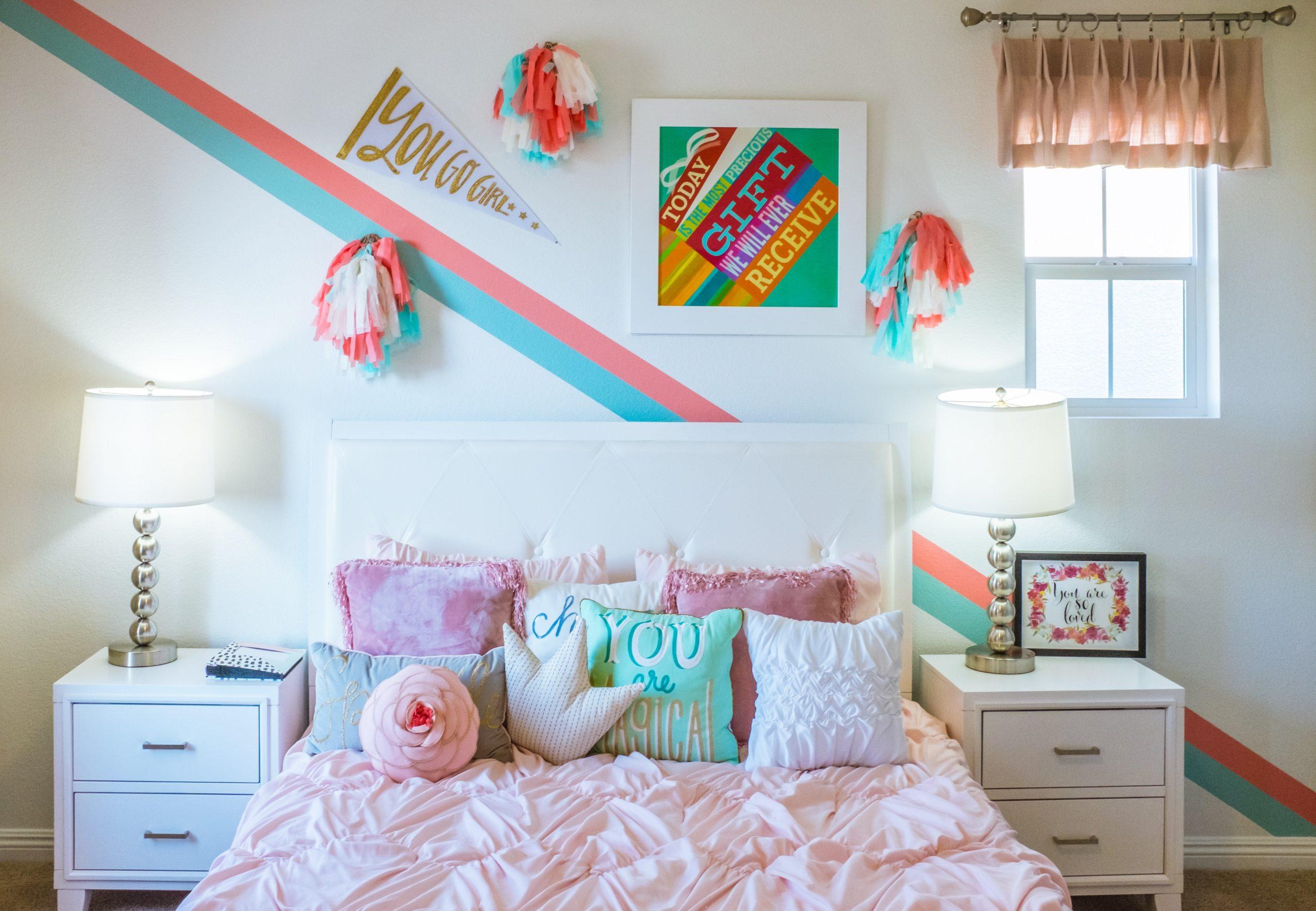 Na foto um quarto de menina com decorações coloridas na parede.