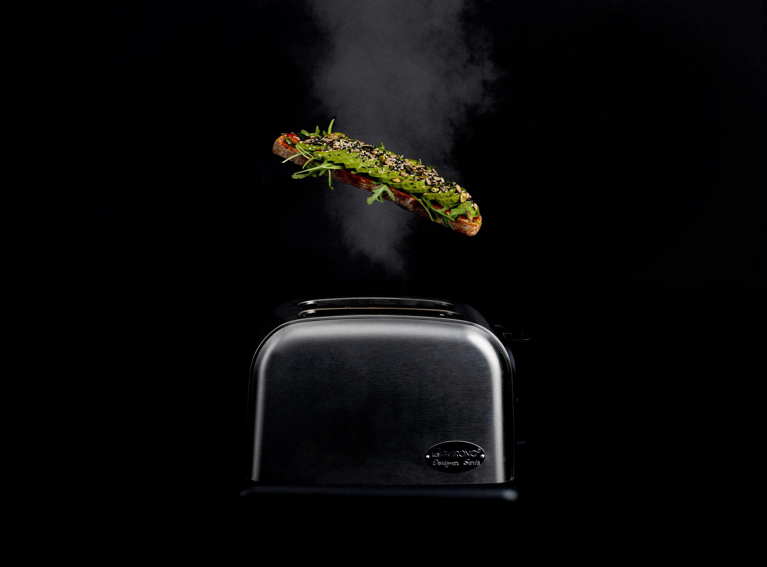 Na foto um torradeira com uma torrada em cima no ar.